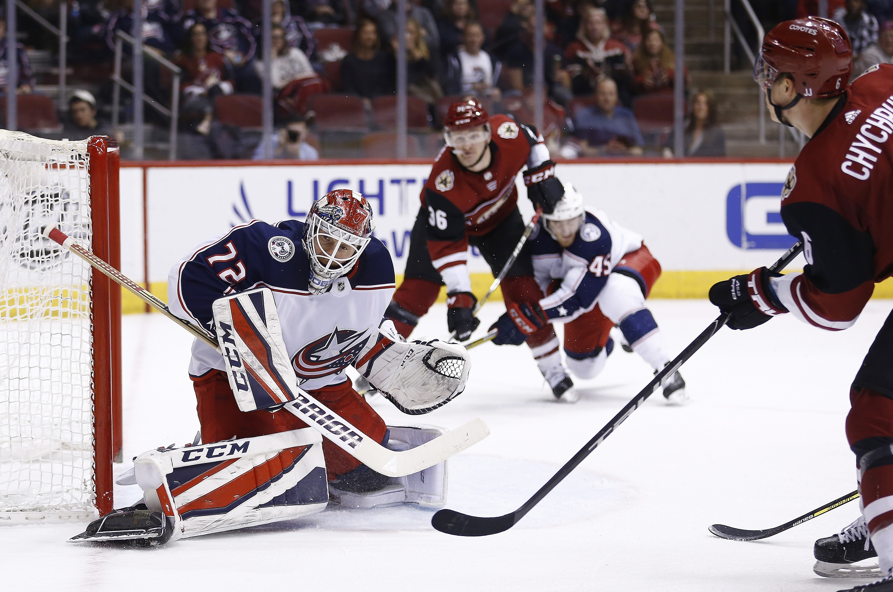 Columbus Blue Jackets goaltender Sergei Bobrovsky (72) makes a save on a shot by Arizona Coyotes defenseman Jakob Chychrun, right, during the second period of an NHL hockey game, Thursday, Jan. 25, 2018, in Glendale, Ariz. (AP Photo/Ross D. Franklin)