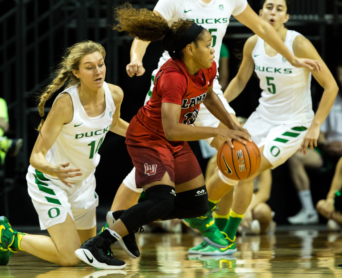 Lamar Cardinals guard Chastadie Barrs (#10) escapes as Ducks forward Lydia Giomi (#14) falls to the ground. The Oregon Ducks Women's basketball team won their season opener against the Lamar Cardinals 84-67.  Photo by Austin Hicks, Oregon News Lab
