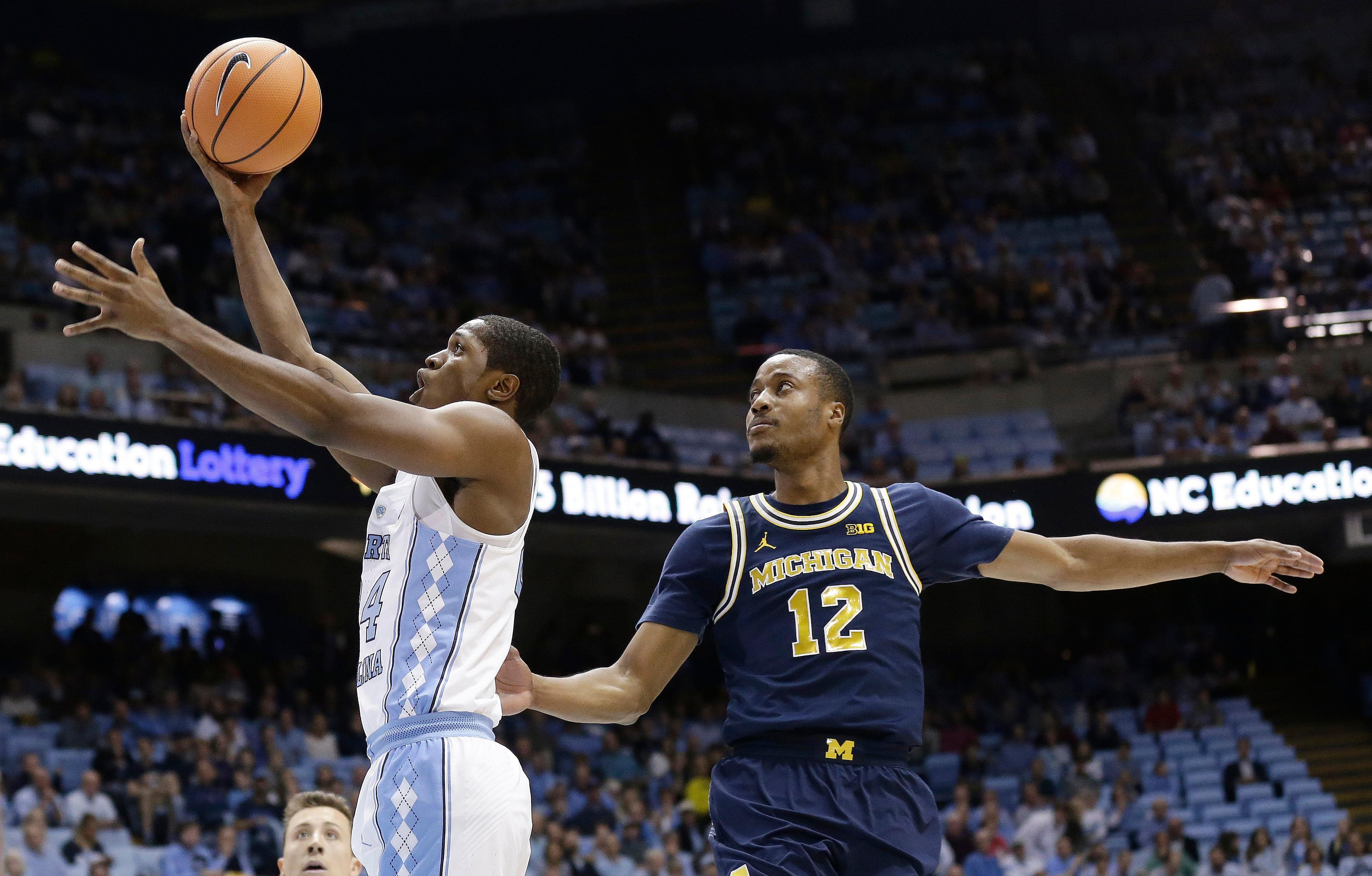North Carolina's Kenny Williams drives to the basket while Michigan's Muhammad-Ali Abdur-Rahkman (12) defends during the first half of an NCAA college basketball game in Chapel Hill, N.C., Wednesday, Nov. 29, 2017. (AP Photo/Gerry Broome)