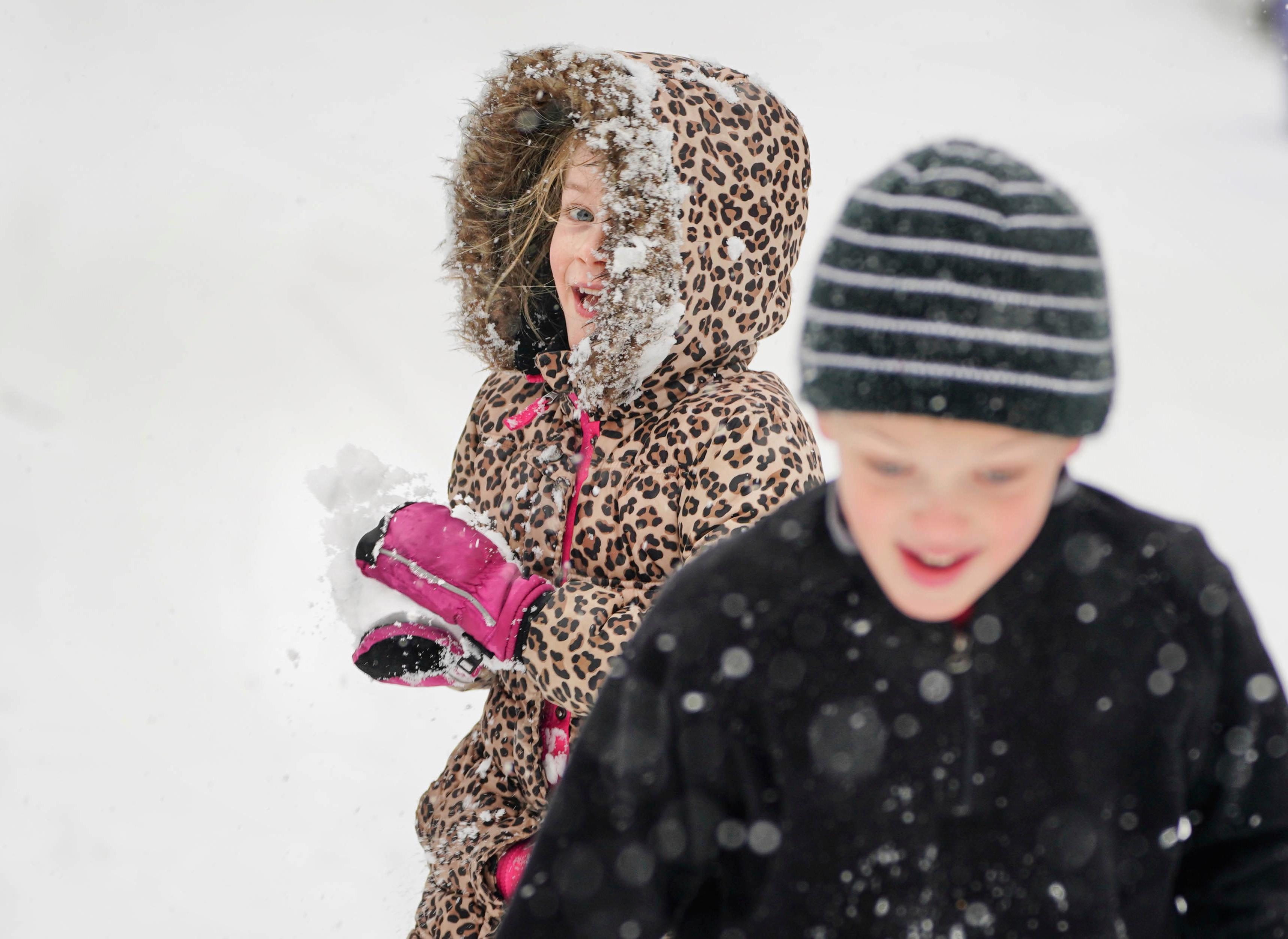 Alma Connoy, 7, left, and her brother Graham Connoy, 8, spent their spring break shoveling and enjoying an epic and good natured snowball fight. Unrelenting snowfall was expected all day, making the commute home challenging in Minnesota's Twin Cities and other locations. (Glen Stubbe/Star Tribune via AP)