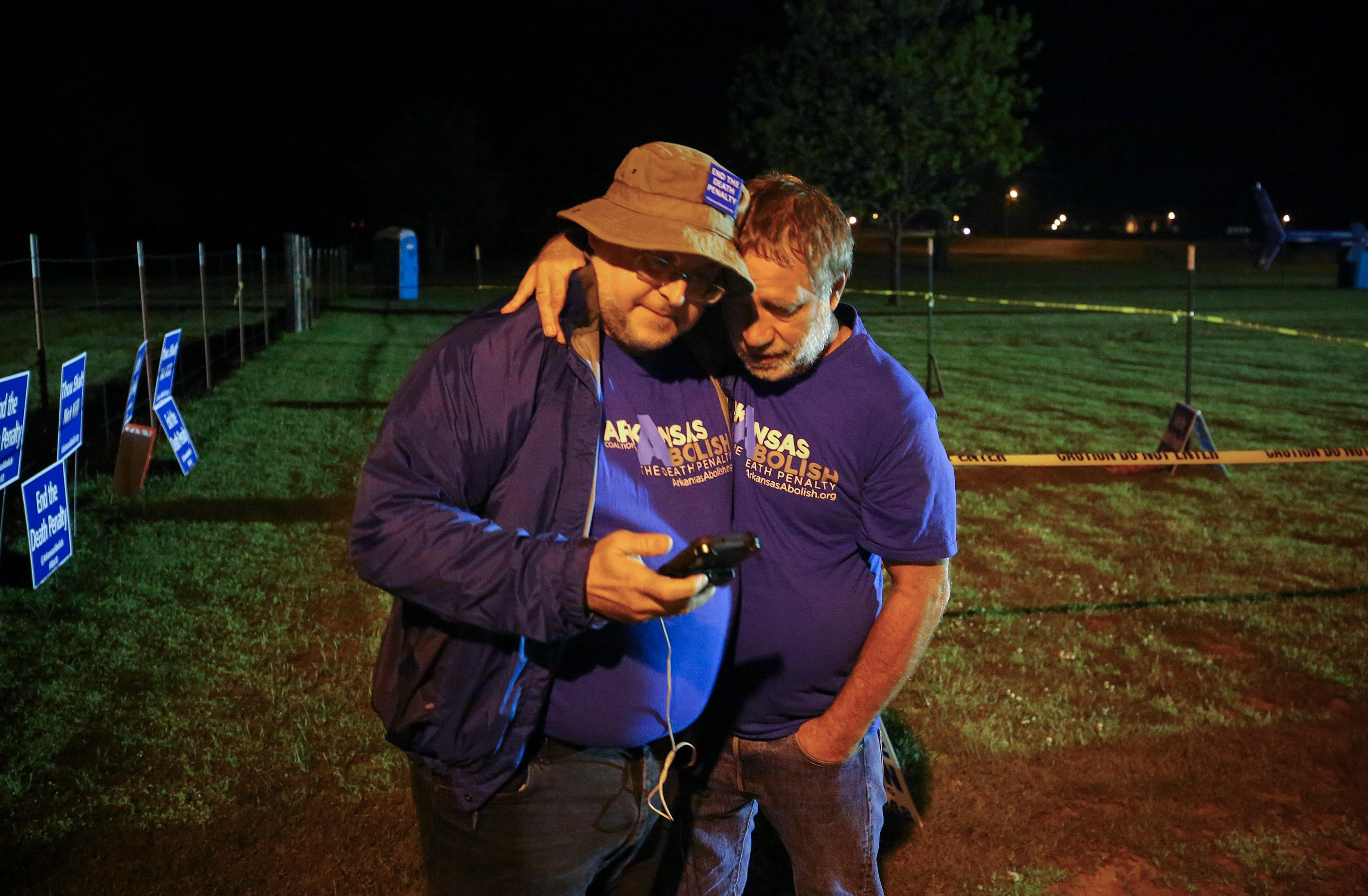 "Anti-death penalty supporter Randy Gardner, right, embraces Abraham Bonowitz, left, after they read on his phone the 11:45 p.m., decision to halt the execution in their taped off ""protest corral"" outside the Varner Unit late Monday, April 17, 2017 near Varner, Ark. (Stephen B. Thornton /The Arkansas Democrat-Gazette via AP)"