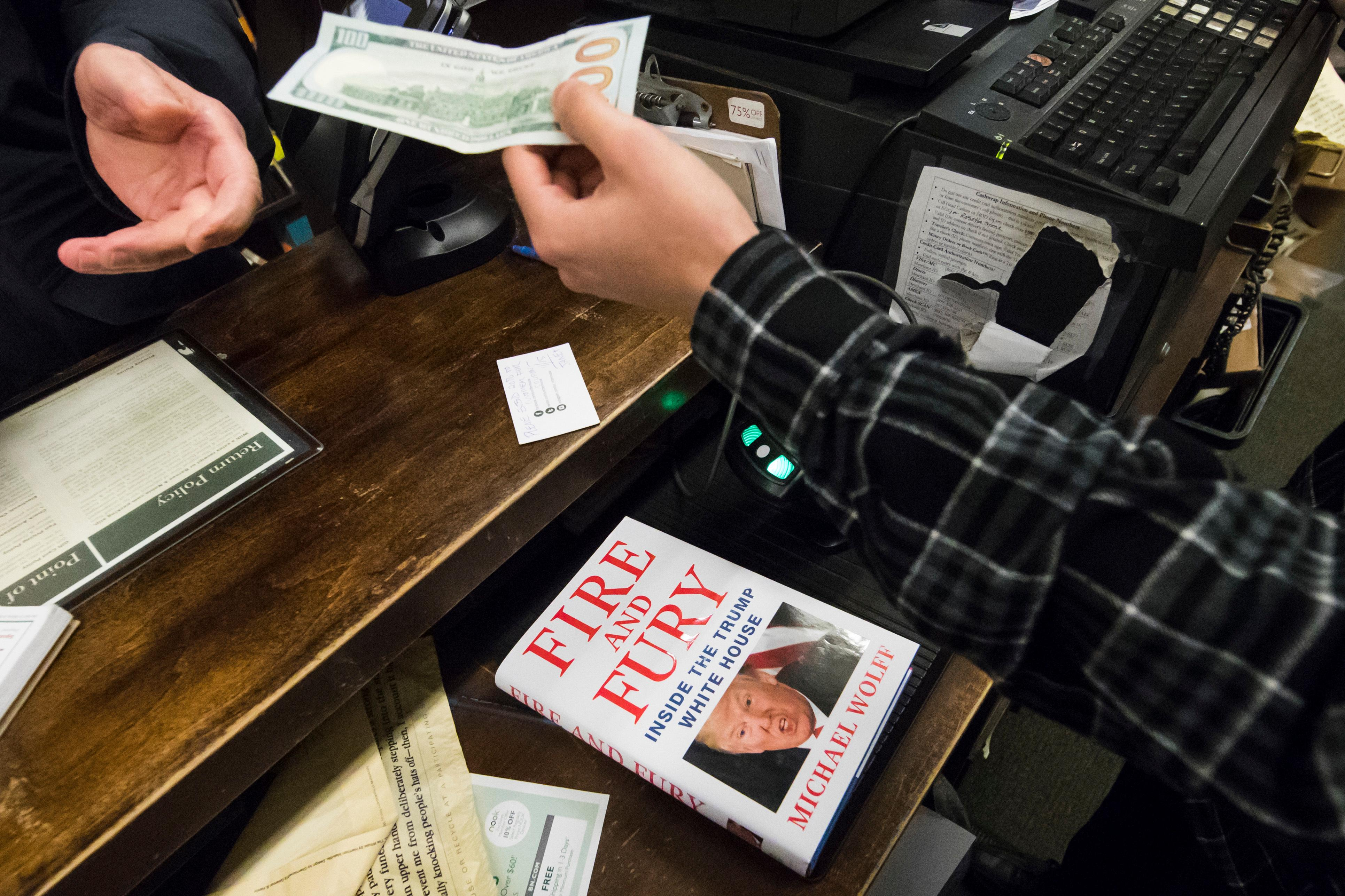 "A salesperson takes money to ring up a copy of the book ""Fire and Fury: Inside the Trump White House"" by Michael Wolff at a Barnes & Noble store in Philadelphia, Friday, Jan. 5, 2018. (AP Photo/Matt Rourke)"