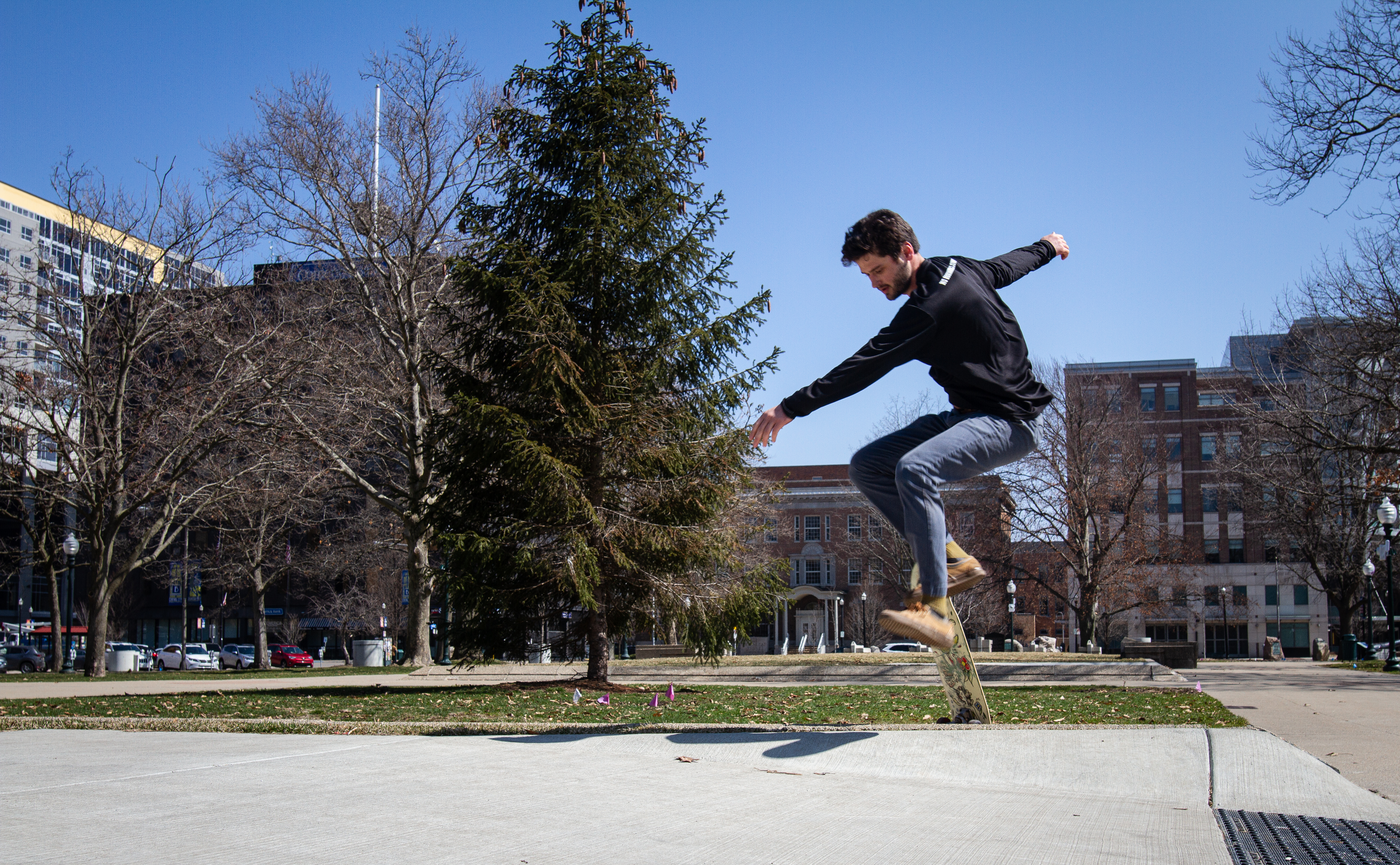 Kalamazoo resident Alex Maile skateboards at Bronson Park in Kalamazoo on Wednesday, March 25, 2020. While Michigan is under a stay-at-home order to prevent the spread of COVID-19, many individuals are using the order as an opportunity to enjoy the outdoors while also practicing safe social distancing. (WWMT/Sarah White)