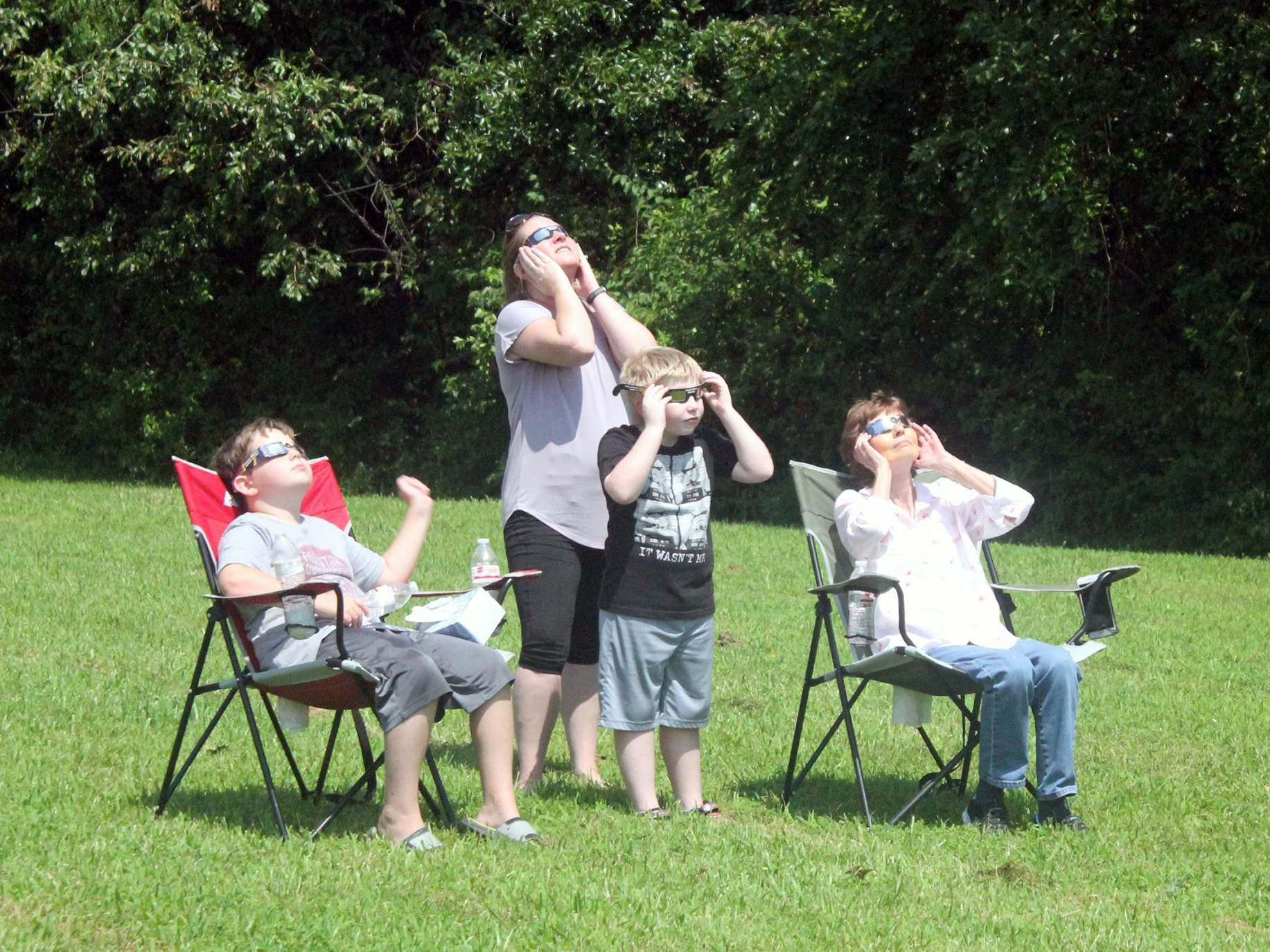 The Hammett family of Independence checks out the end of the partial eclipse before totality at George Owens Nature Park in Independence. [Mike Genet/The Examiner]