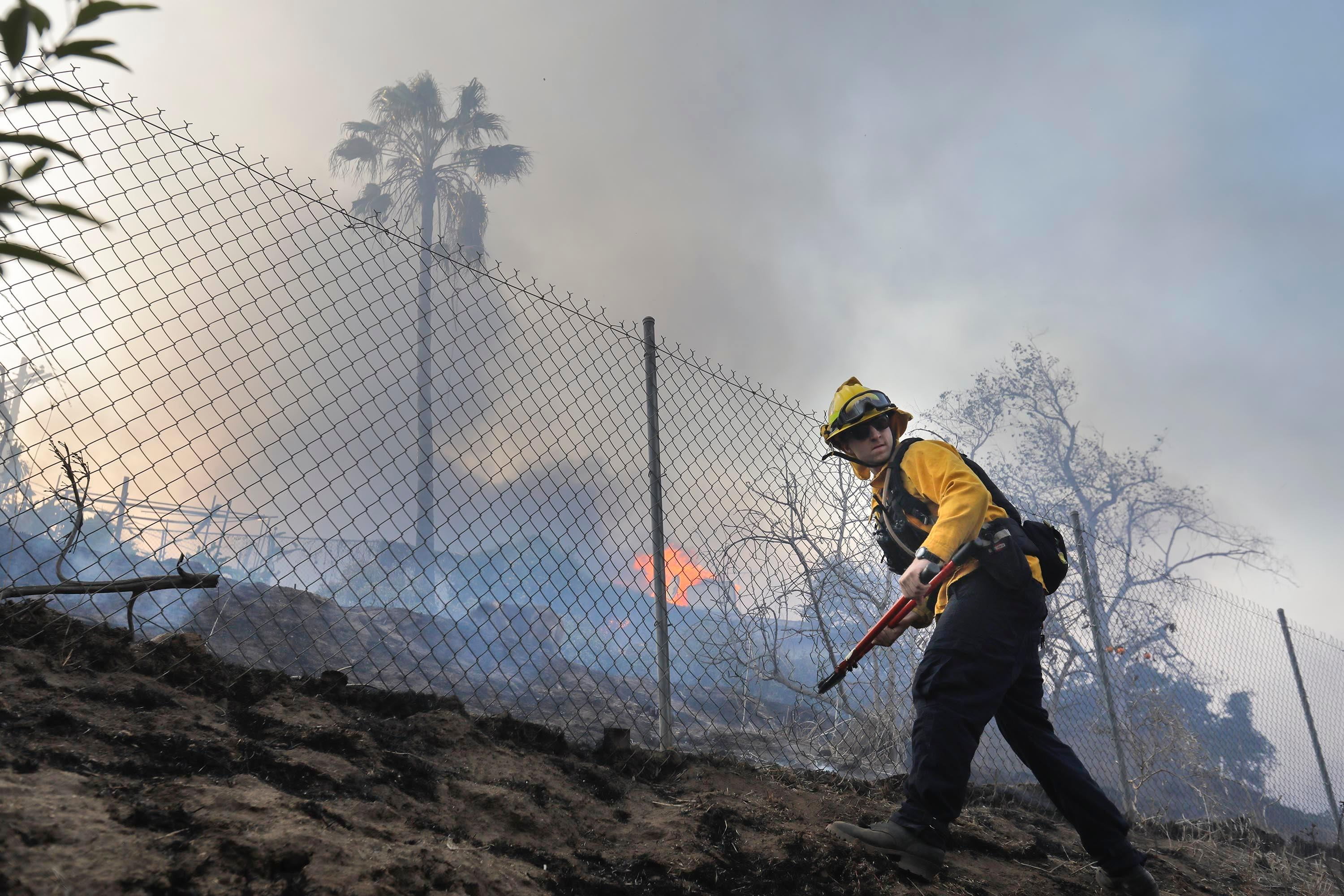 "A Vista firefighter cuts a hole in a fence at a home on West Lilac Road in Bonsall, Calif., Thursday, Dec, 7, 2017.  The biggest and most destructive of the windblown fires raking Southern California shut down one of the region's busiest freeways Thursday and threatened Ojai, a scenic mountain town dubbed ""Shangri-La"" and known for its boutique hotels and New Age spiritual retreats.  (Howard Lipin/The San Diego Union-Tribune via AP)"