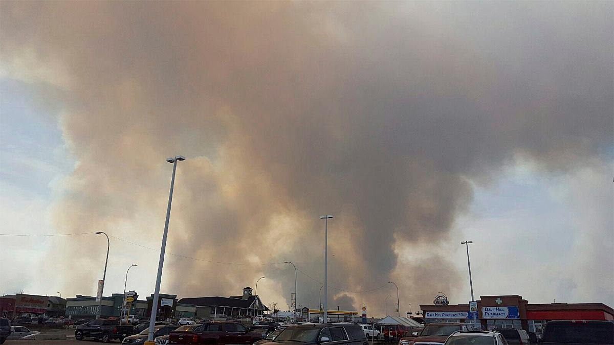 Smoke rises from a wildfire outside of Fort McMurray, Alberta, Tuesday, May 3, 2016. The entire population of the Canadian oil sands city of Fort McMurray, has been ordered to evacuate as a wildfire whipped by winds engulfed homes and sent ash raining down on residents. (Mary Anne Sexsmith-Segato/The Canadian Press via AP) MANDATORY CREDIT