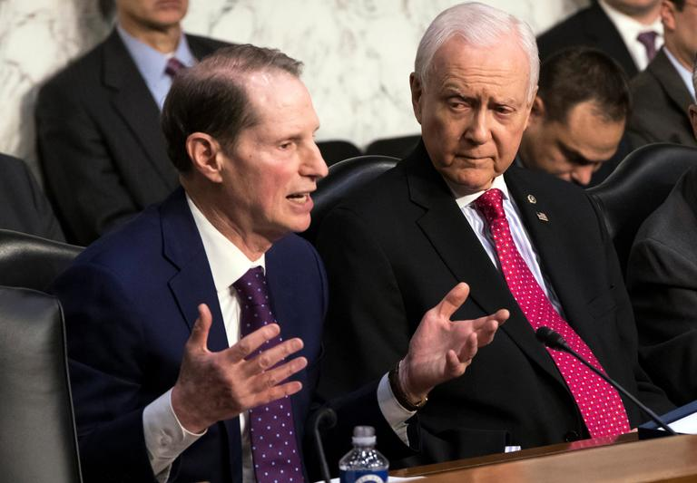 Sen. Ron Wyden, D-Ore., left, the top Democrat on the Senate Finance Committee, criticizes the Republican tax reform plan while Chairman Orrin Hatch, R-Utah, listens to his opening statement as the panel begins work overhauling the nation's tax code, on Capitol Hill in Washington, Monday, Nov. 13, 2017. The legislation in the House and Senate carries high political stakes for President Donald Trump and Republican leaders in Congress, who view passage of tax cuts as critical to the GOP's success at the polls next year. (AP Photo/J. Scott Applewhite)