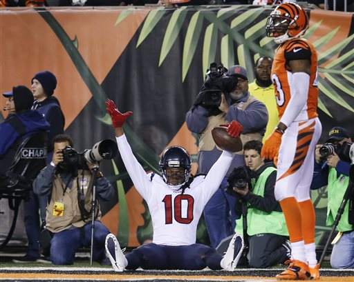 Houston Texans wide receiver DeAndre Hopkins (10) celebrates after scoring a touchdown as Cincinnati Bengals strong safety George Iloka (43) stands to the side in the second half of an NFL football game in Cincinnati, Monday, Nov. 16, 2015.  (AP Photo/Frank Victores)