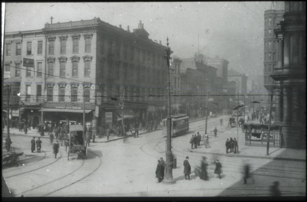 <p>On the western edge of Government Square is the NW corner of Fifth and Walnut Streets. This photograph, believed to have been taken in the 1890s, shows the corner looking northwest. Streetcars and horse-drawn carriages glide through the intersection as people mingle in the streets. / From the collection of the Public Library of Cincinnati and Hamilton County / Image courtesy of the Public Library of Cincinnati and Hamilton County // Published: 9.27.18</p>
