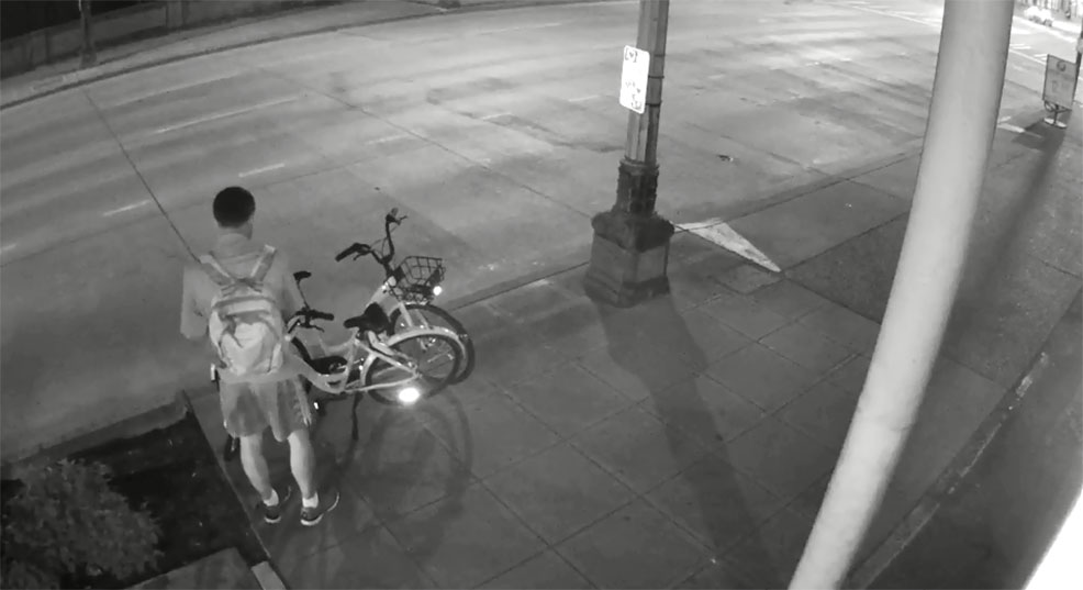 Screenshot from security video shows a man apparently sabotaging the brakeline of a bike share bicycle in SoDo. (Photo credit: Seattle Police Dept.)