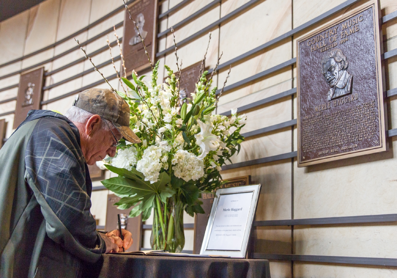 "Pete Robichaux of New Orleans writes his condolences about the death of Merle Haggard at the Country Music Hall of Fame in Nashville, Tenn., on Wednesday, April 6, 2016. Haggard, who rose from poverty and prison to international fame through his songs about outlaws, underdogs and an abiding sense of national pride in such hits as ""Okie From Muskogee"" and ""Sing Me Back Home,"" died Wednesday at 79, on his birthday.  (AP Photo/Erik Schelzig)"