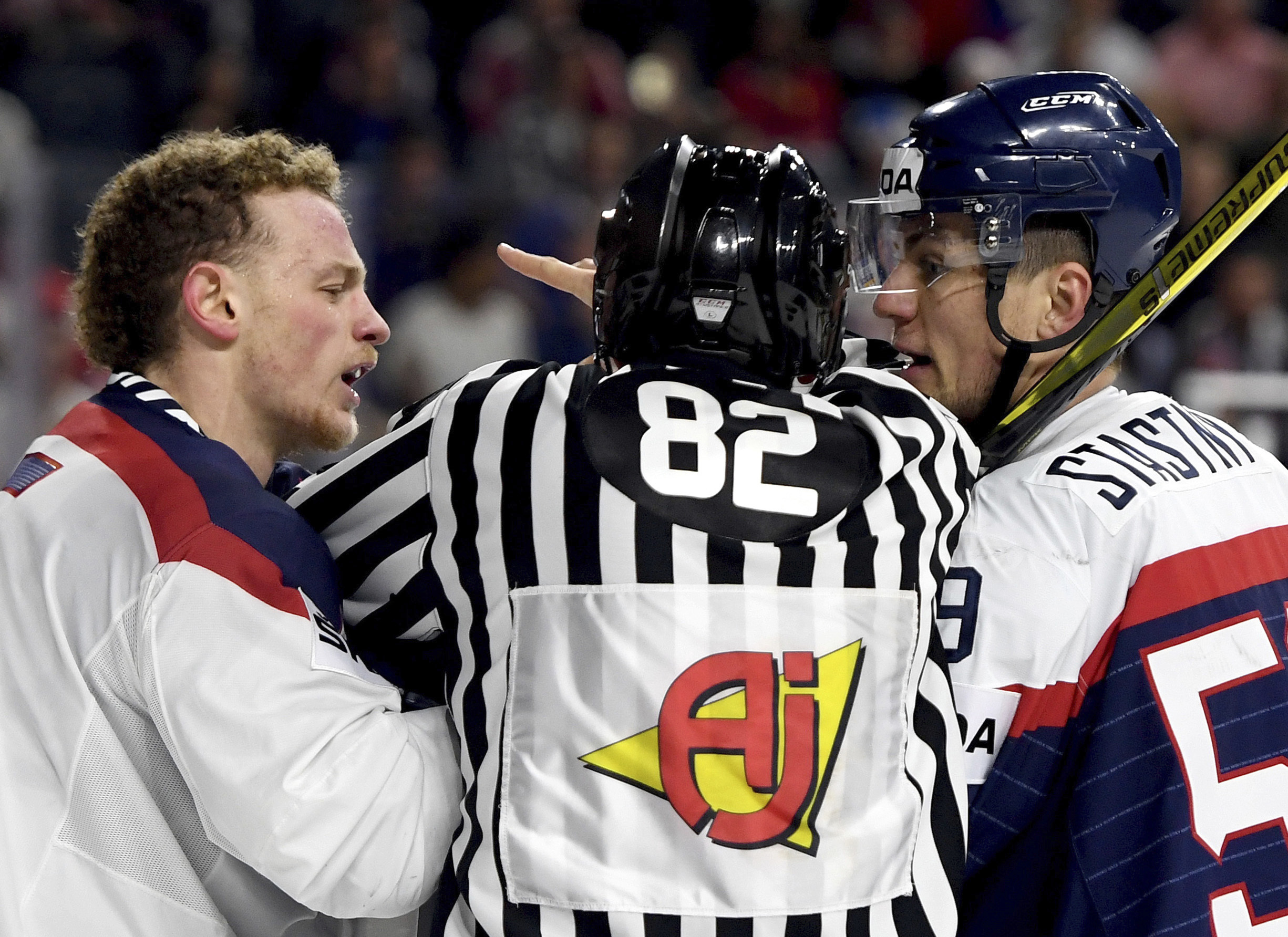 Slovakia's Andrej Stastny, right, and US player Jack Eichel, left, and the referee scuffle during a group A match between Slovakia and USA at the 2017 Hockey World Championships in the Lanxess Arena in  Cologne, Germany, Sunday, May 14, 2017.  (Monika Skolimowska/dpa via AP)