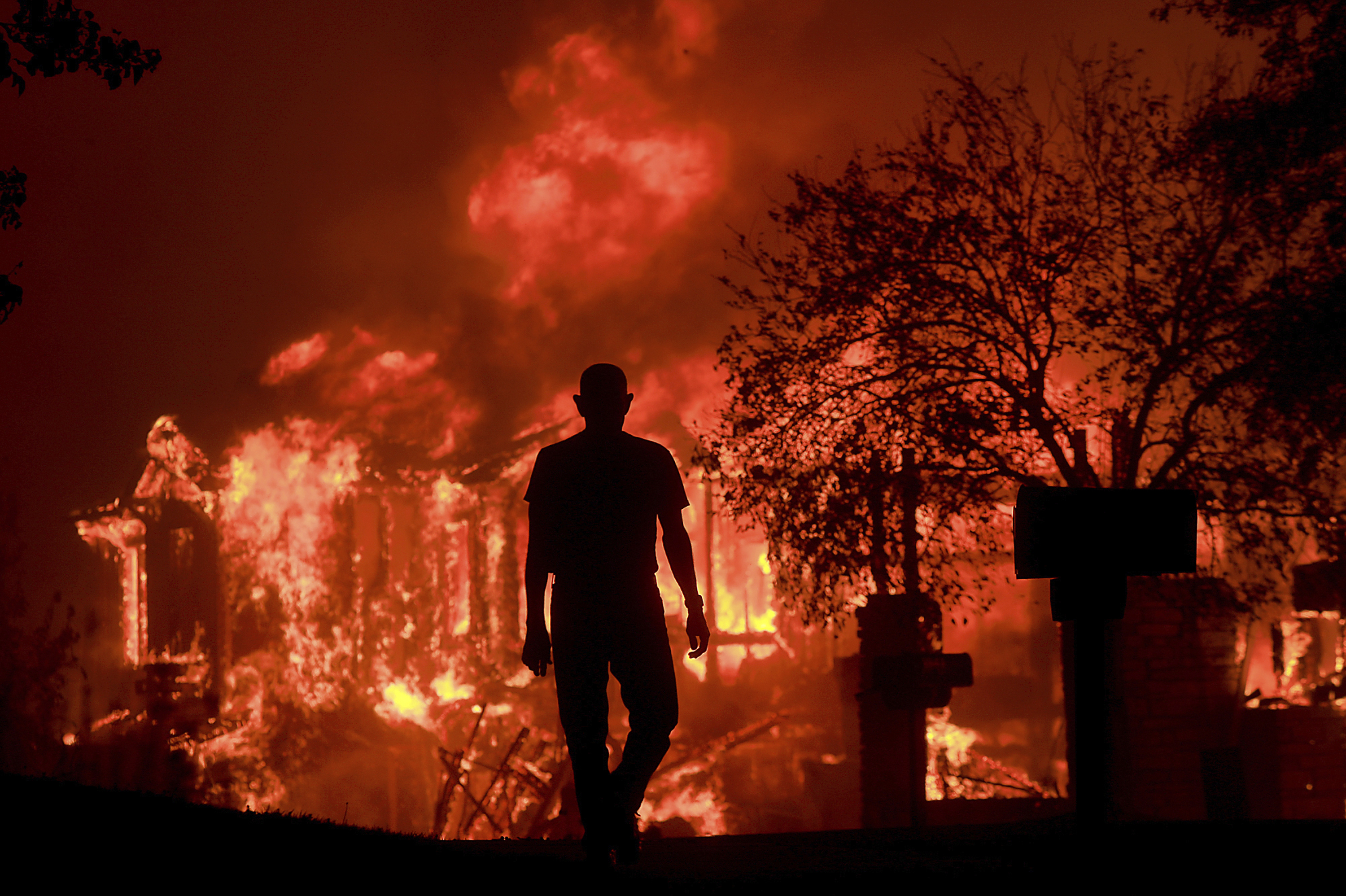 FILE - In this Oct. 9, 2017 file photo, Jim Stites watches part of his neighborhood burn in Fountain Grove, Calif. California's insurance commissioner said Tuesday, Oct. 31, 2017 that losses from a series of destructive wildfires now exceed $3.3 billion. Commissioner Dave Jones said Tuesday, Oct. 31, 2017, that the figure represents claims for homes and businesses insured by 15 major insurers. (Kent Porter/The Press Democrat via AP, File)