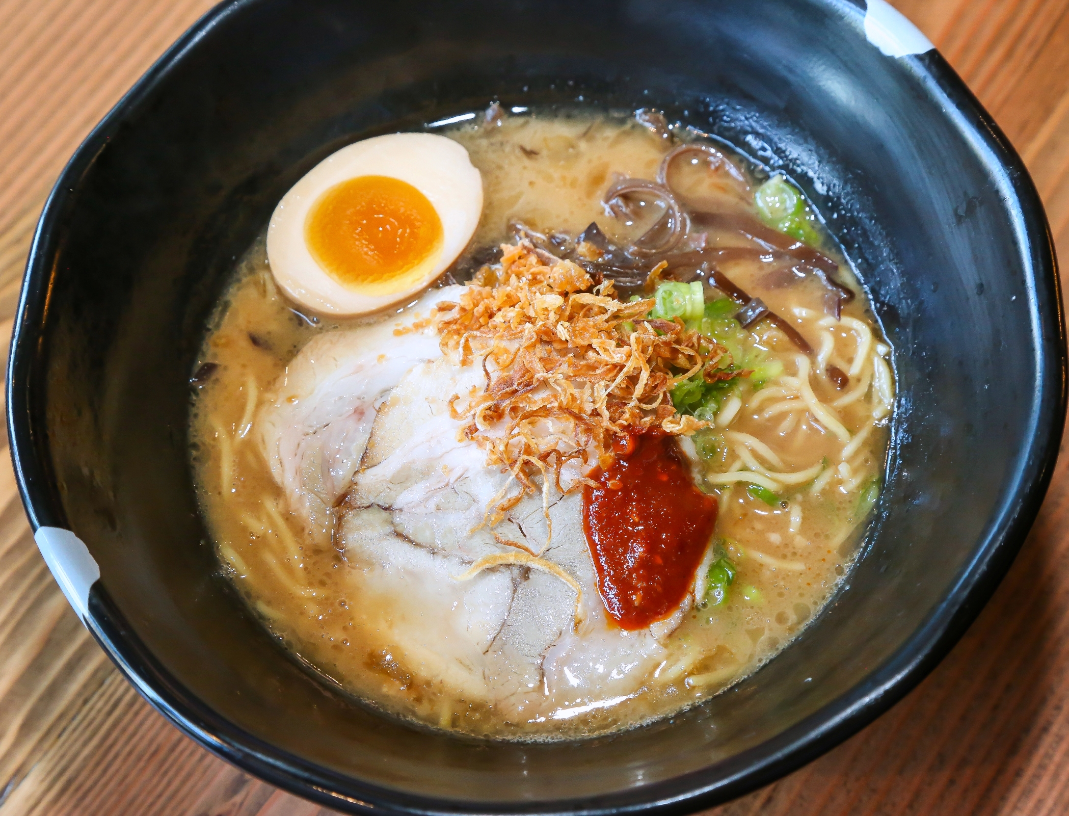 Though the menu is quite expansive, JINYA specializes in authentic Tonkotsu ramen, with a focus on flavorful broth; the food preparation process includes simmering the broth for over 12 hours. (Image: Peter Stepanek)