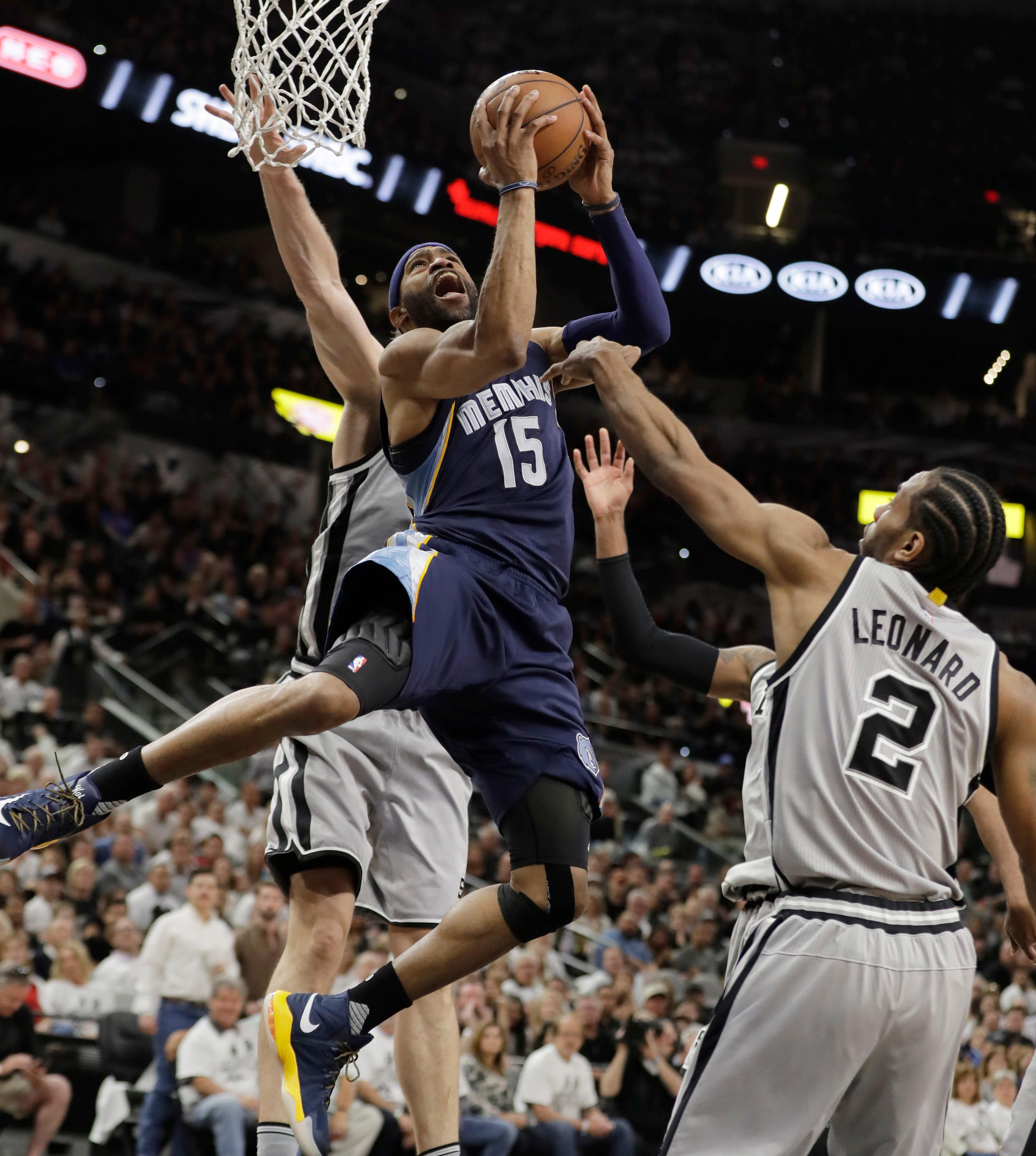 Memphis Grizzlies guard Vince Carter (15) shoots over San Antonio Spurs forward Kawhi Leonard (2) during the first half of Game 1 in a first-round NBA basketball playoff series, Saturday, April 15, 2017, in San Antonio. (AP Photo/Eric Gay)
