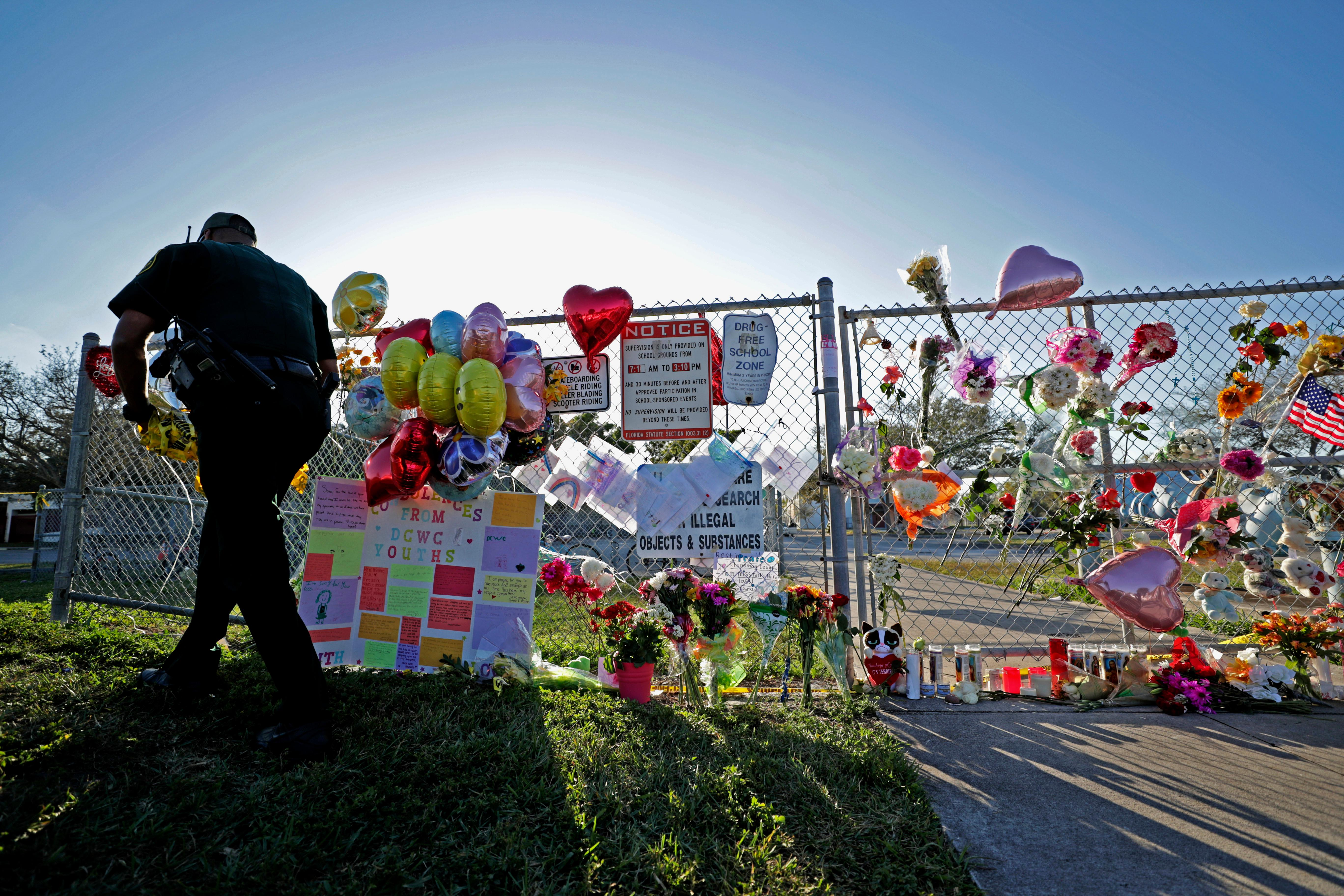 A Broward County Sheriff's Office deputy removes police tape from a makeshift memorial at Marjory Stoneman Douglas High School in Parkland, Fla., Sunday, Feb. 18, 2018. Nikolas Cruz, a former student, was charged with 17 counts of premeditated murder on Thursday. (John McCall/South Florida Sun-Sentinel via AP)