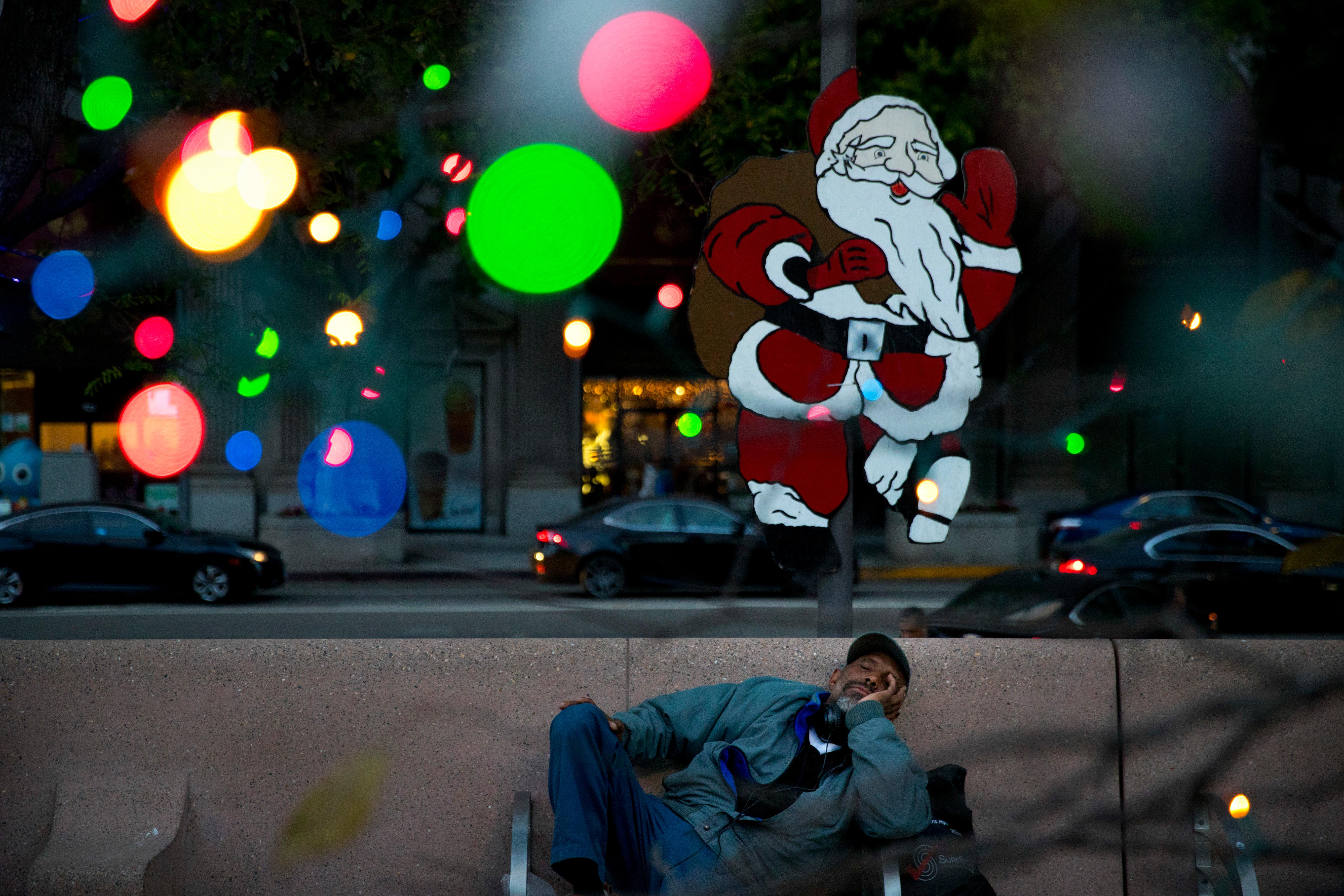 Homeless man Alonzo Harrison, 47, takes a nap on a bench at Pershing Square decorated with Christmas lights in the background on Monday, Dec. 4, 2017, in Los Angeles. A homeless crisis of unprecedented proportions is rocking the West Coast, and its victims are being left behind by the very things that mark the region's success: soaring housing costs, rock-bottom vacancy rates and a roaring economy that waits for no one. (AP Photo/Jae C. Hong)