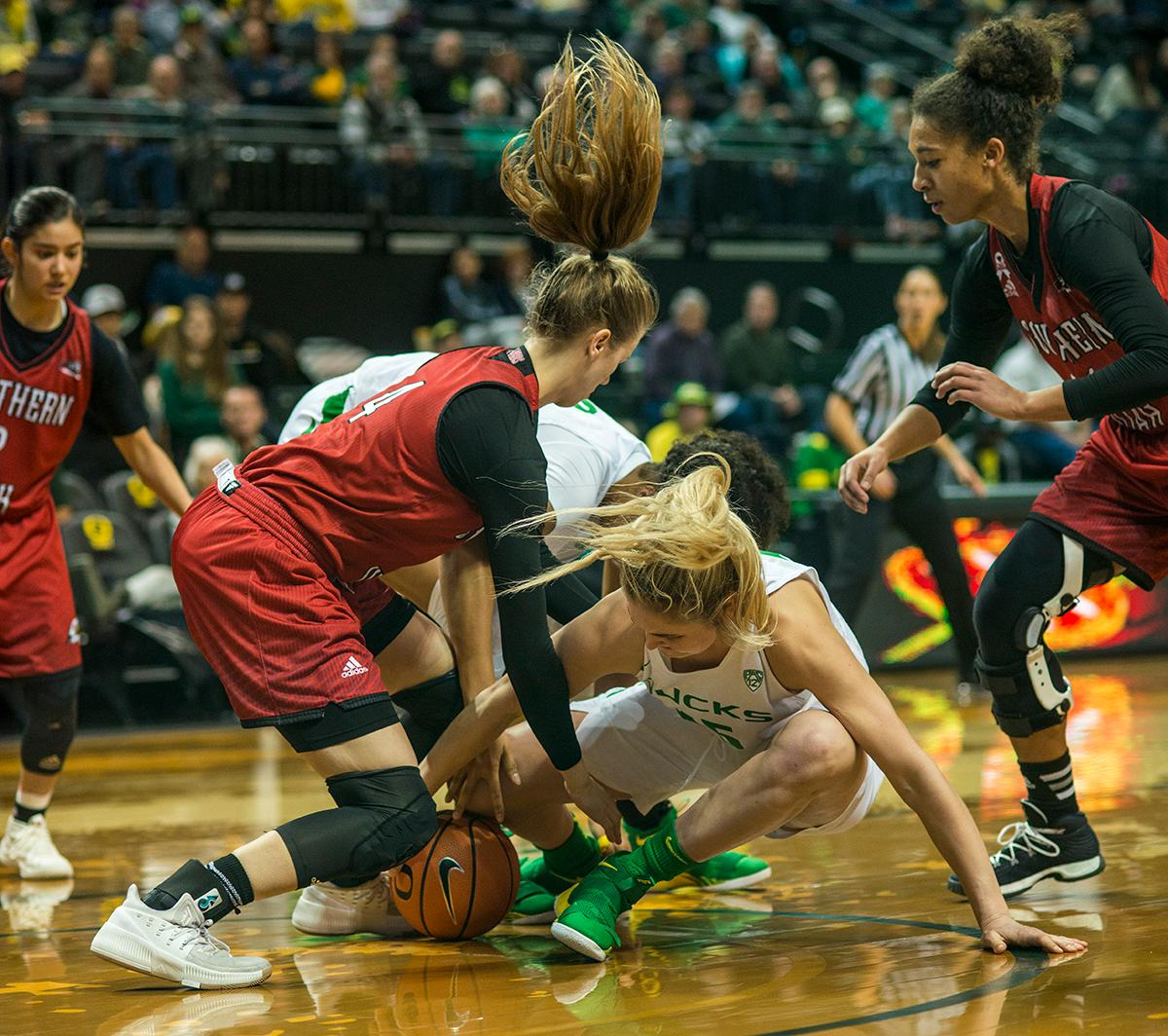 The Oregon Ducks and Southern Utah Thunderbirds struggle on the ground for a loose ball. The University of Oregon Ducks women basketball team defeated the Southern Utah Thunderbirds 98-38 in Matthew Knight Arena Saturday afternoon. The Ducks had four players in double-digits: Ruthy Hebard with 13; Mallory McGwire with 10; Lexi Bando with 17 which included four three-pointers; and Sabrina Ionescu with 16 points. The Ducks overwhelmed the Thunderbirds, shooting 50% in field goals to South Utah's 26.8%, 53.8% in three-pointers to 12.5%, and 85.7% in free throws to 50%. The Ducks, with an overall record of 8-1, and coming into this game ranked 9th, will play their next home game against Ole Miss on December 17. Photo by Rhianna Gelhart, Oregon News Lab