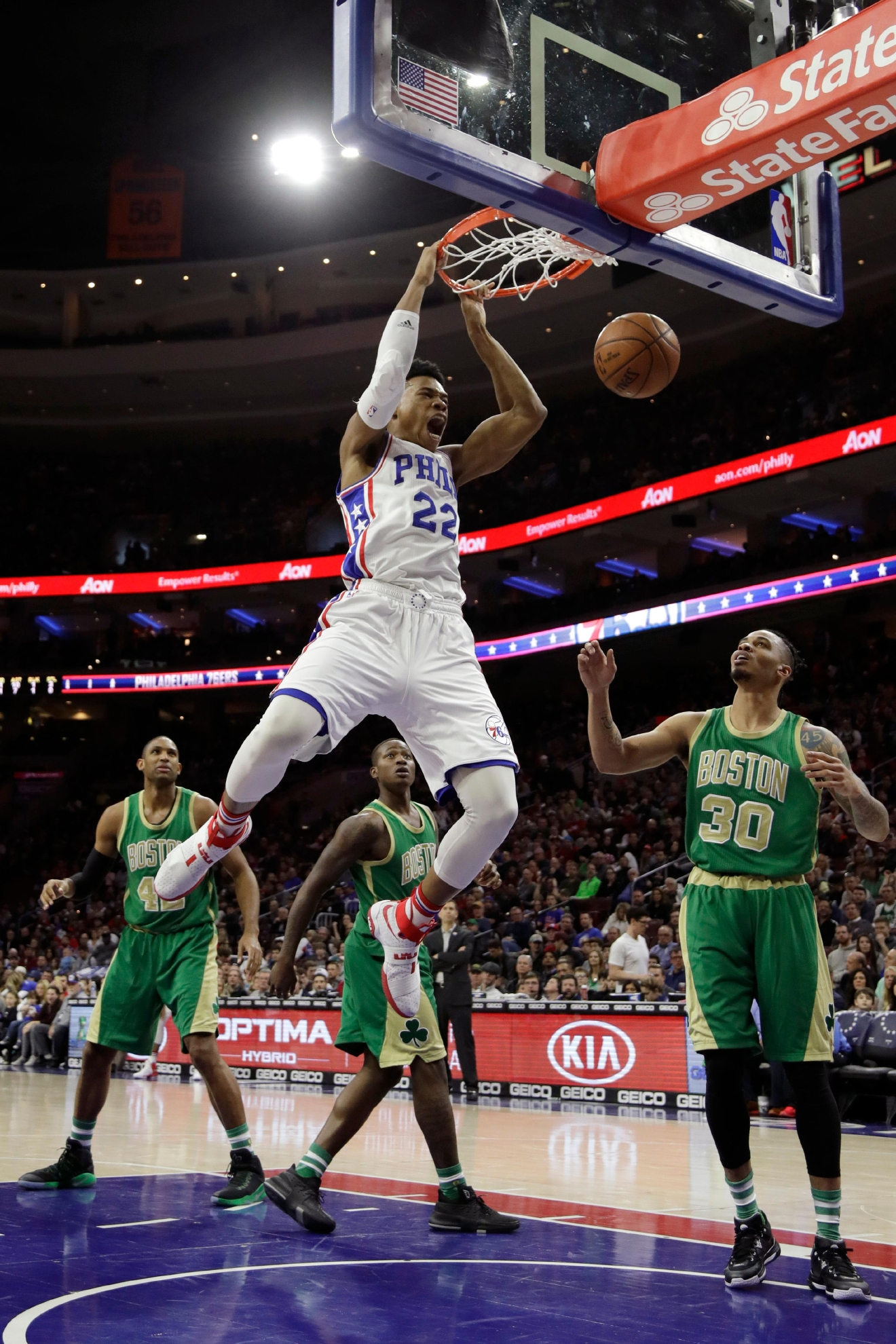 Philadelphia 76ers' Richaun Holmes (22) dunks the ball as Boston Celtics' Gerald Green (30) looks on during the first half of an NBA basketball game, Sunday, March 19, 2017, in Philadelphia. (AP Photo/Matt Slocum)