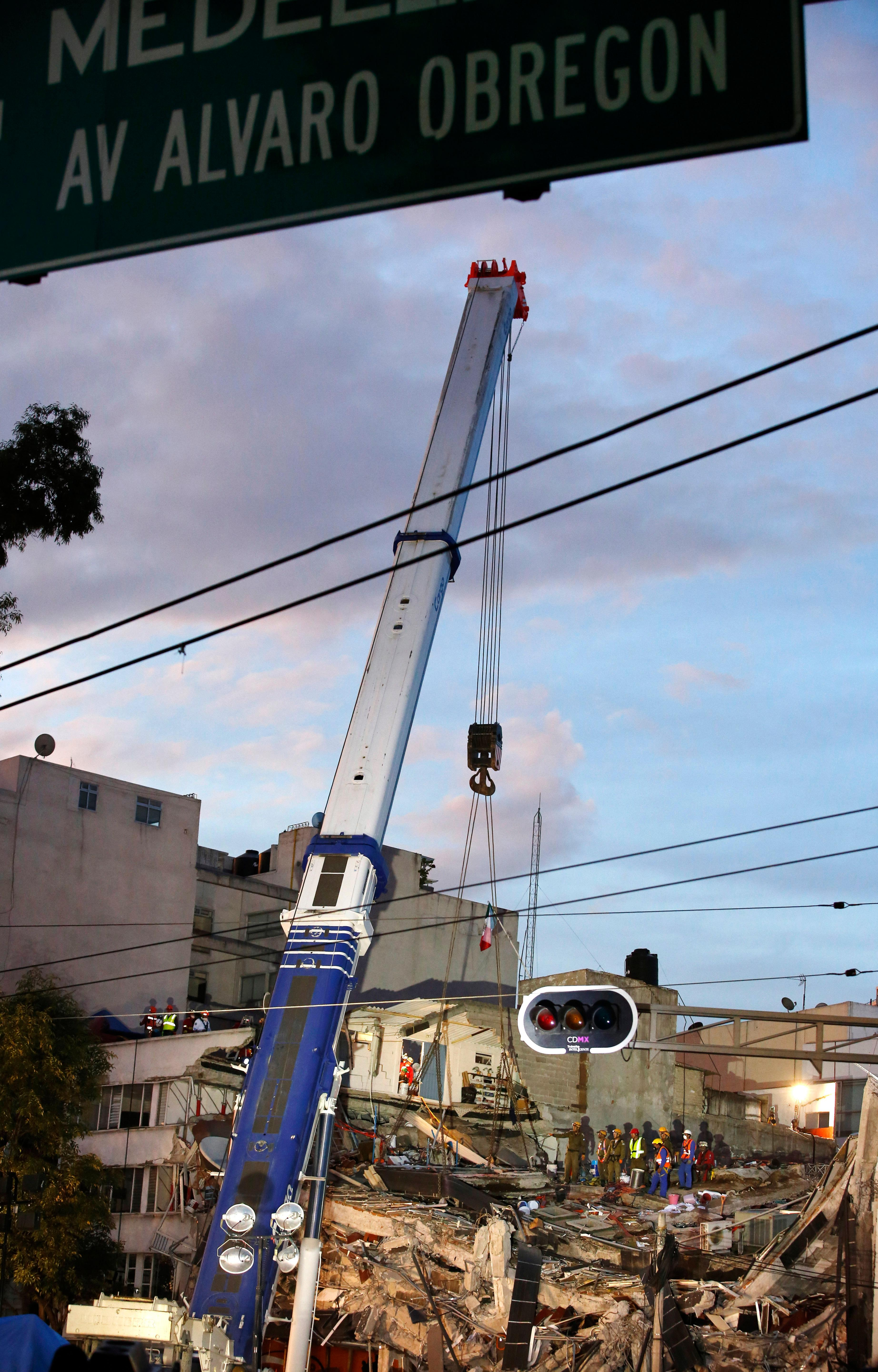 Israeli and Mexican rescue workers use a crane to lift a section of a felled building as rescue workers race against the clock to reach possible survivors trapped inside the office building on Alvaro Obregon Avenue in the Roma Norte neighborhood of Mexico City, at sunrise on Saturday, Sept. 23, 2017. A strong new earthquake shook Mexico on Saturday morning, causing street signs around the collapsed building to sway and rescue workers to evacuate the site temporarily. (AP Photo/Rebecca Blackwell)