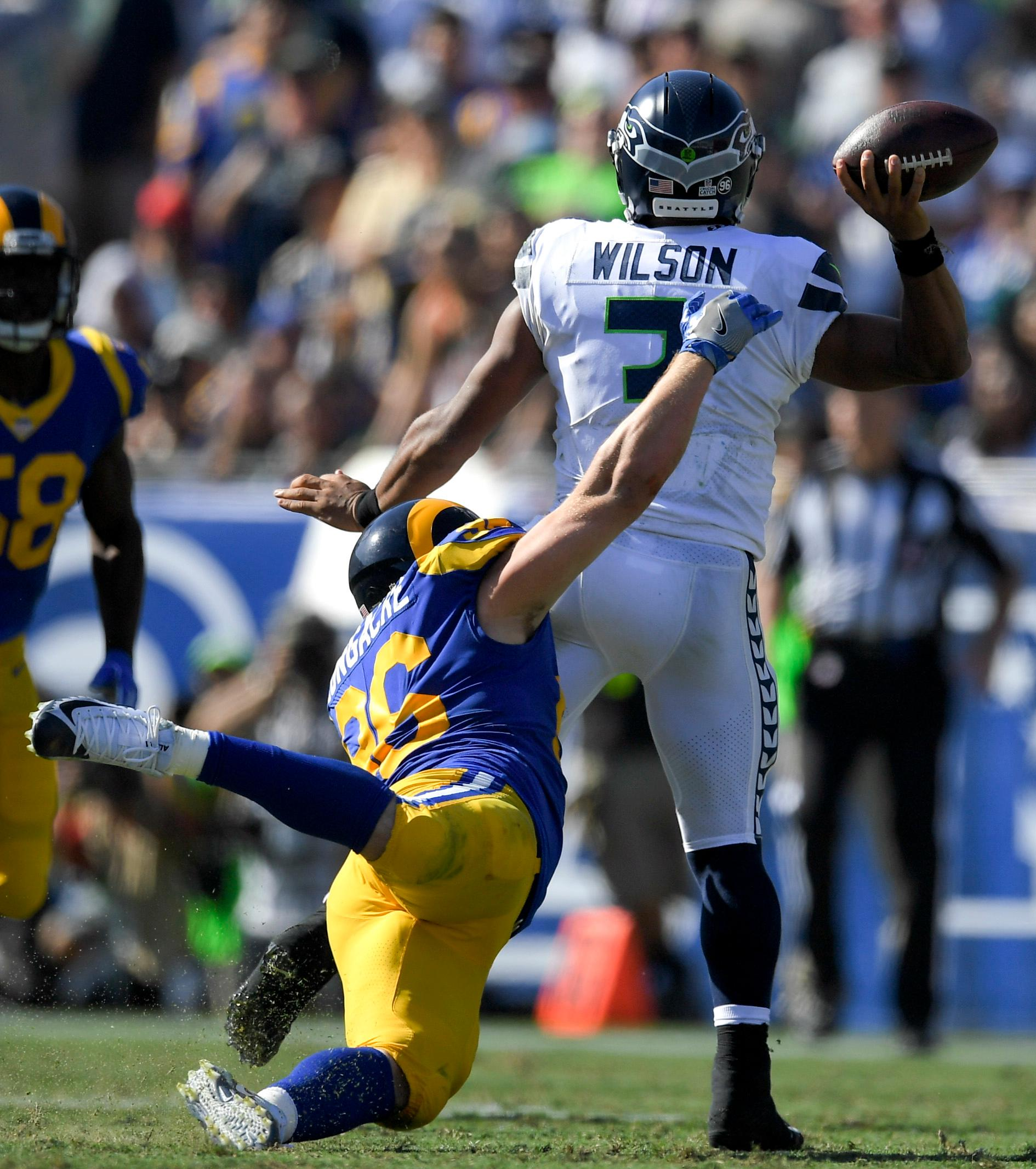 Seattle Seahawks quarterback Russell Wilson gets a pass off under pressure from Los Angeles Rams linebacker Matt Longacre during the second half of an NFL football game Sunday, Oct. 8, 2017, in Los Angeles. (AP Photo/Mark J. Terrill)
