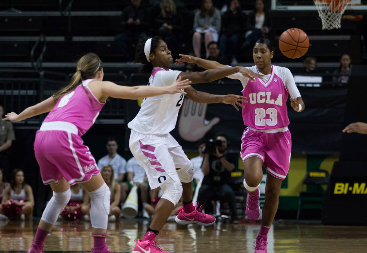 Oregon Ducks forward Ruthy Hebard (#24) passes between UCLA defenders Kelli Hayes (#23) and Kari Korver (#2). The Oregon Ducks defeated the No. 15 UCLA Bruins 84-75 Friday evening at Matthew Knight Arena in Eugene, Oregon.  Photo by Duncan Moore, Oregon News Lab