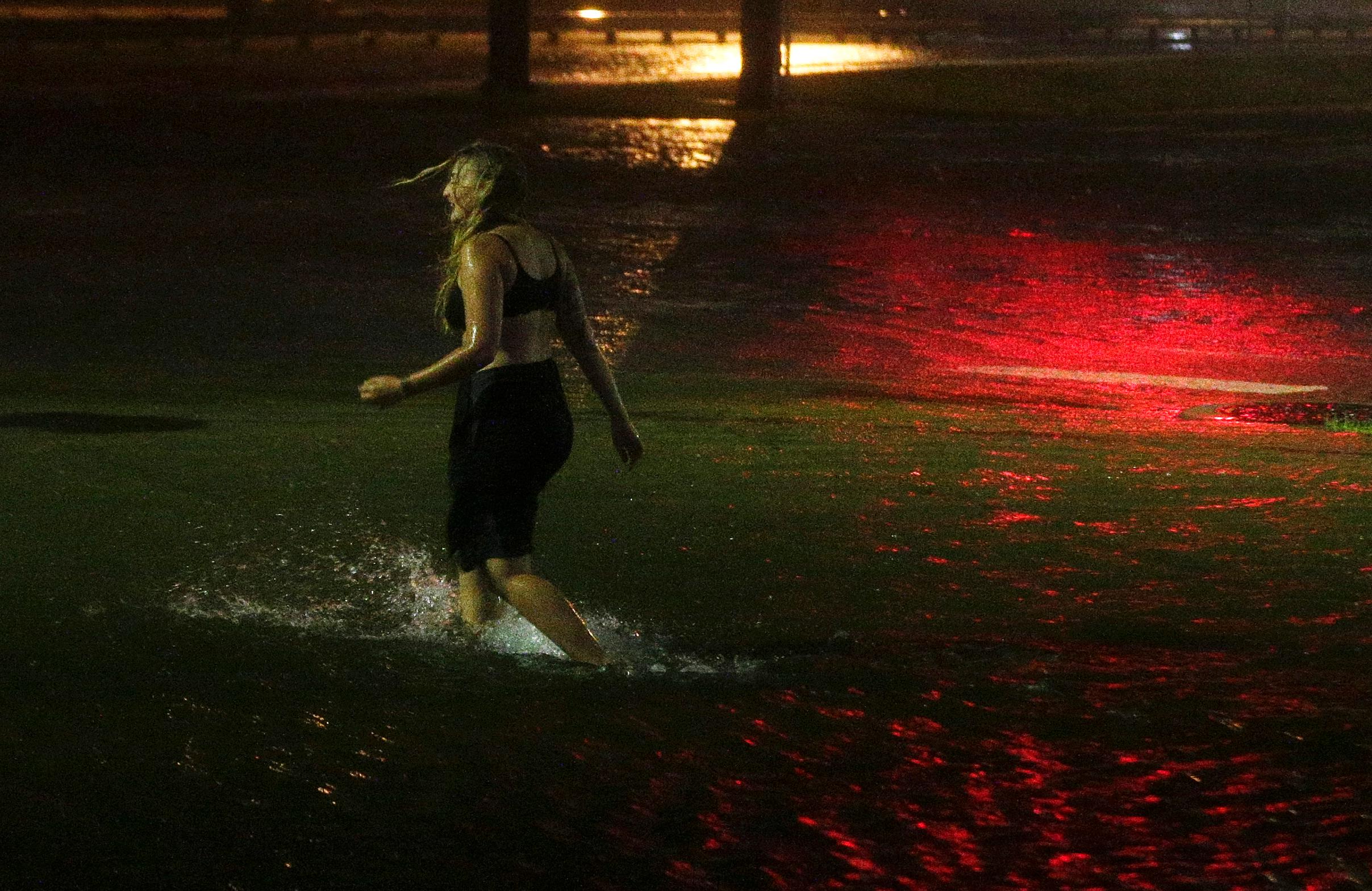 A woman wades through a flooded Water St. in downtown Mobile, Ala., during Hurricane Nate, Sunday, Oct. 8, 2017, in Mobile, Ala.  Hurricane Nate came ashore along Mississippi's coast outside Biloxi early Sunday, the first hurricane to make landfall in the state since Hurricane Katrina in 2005.(AP Photo/Brynn Anderson)