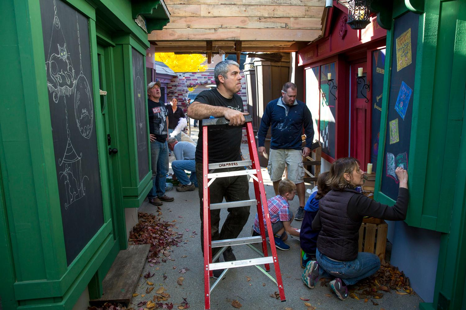 "Jon Chambers, his family, and local community members work on recreating a replica Diagon Alley at his Ballard home to celebrate Halloween and Christmas. ""I've always wanted to do something crazy for Halloween or Christmas,"" said Chambers. ""During Halloween our street is pretty dead, nobody comes down here. This year, a lot of people are going to come down here!"" The Harry Potter replica set will be open to the public through Christmas. (Sy Bean/Seattle Refined)"