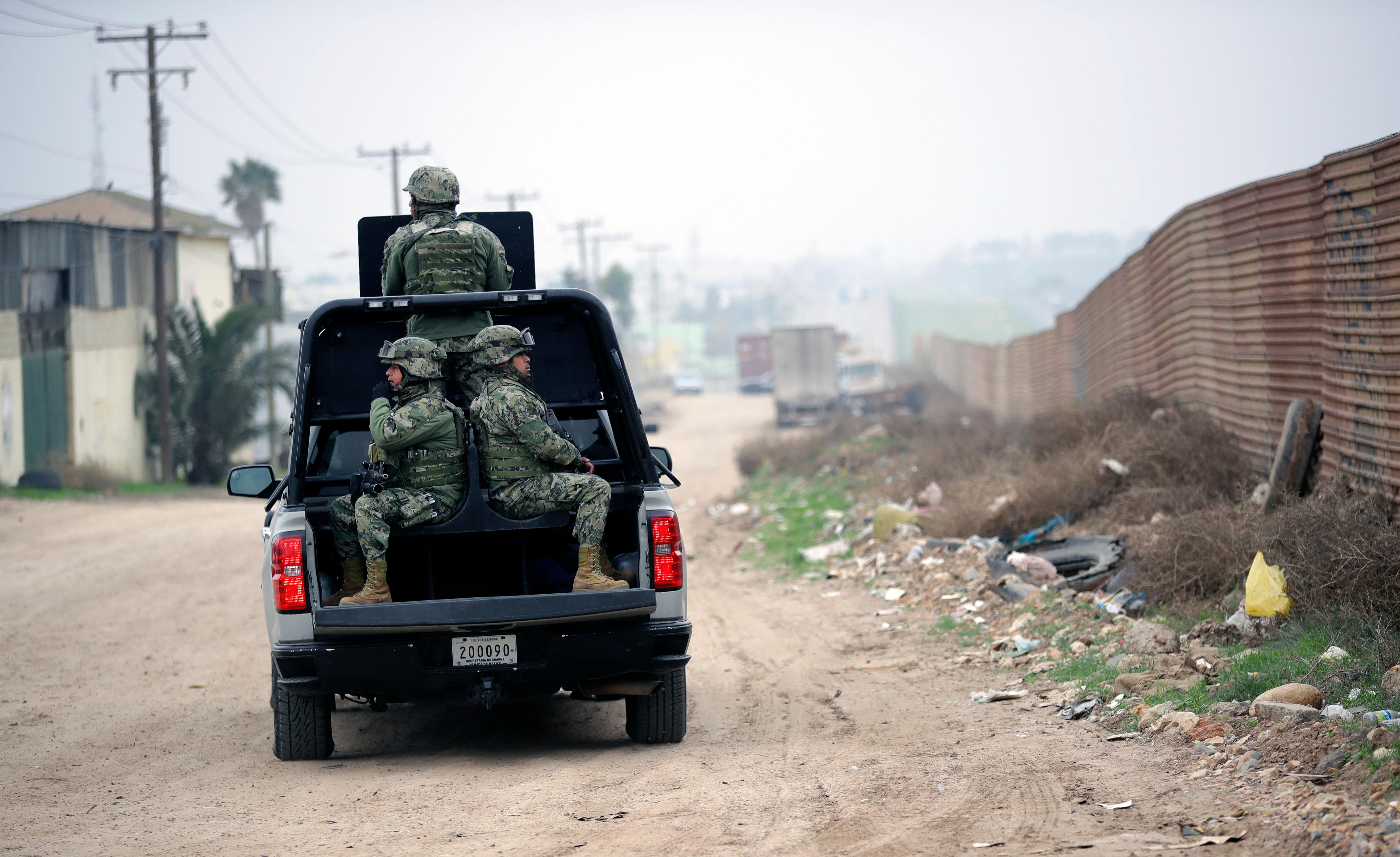 Mexican Navy officers patrol on the Mexico side of the border on Tuesday, March 13, 2018, in Tijuana, Mexico. President Trump is scheduled to visit the site of the border wall prototypes which are on the U.S. side of the wall seen on the right. (AP Photo/Gregory Bull)
