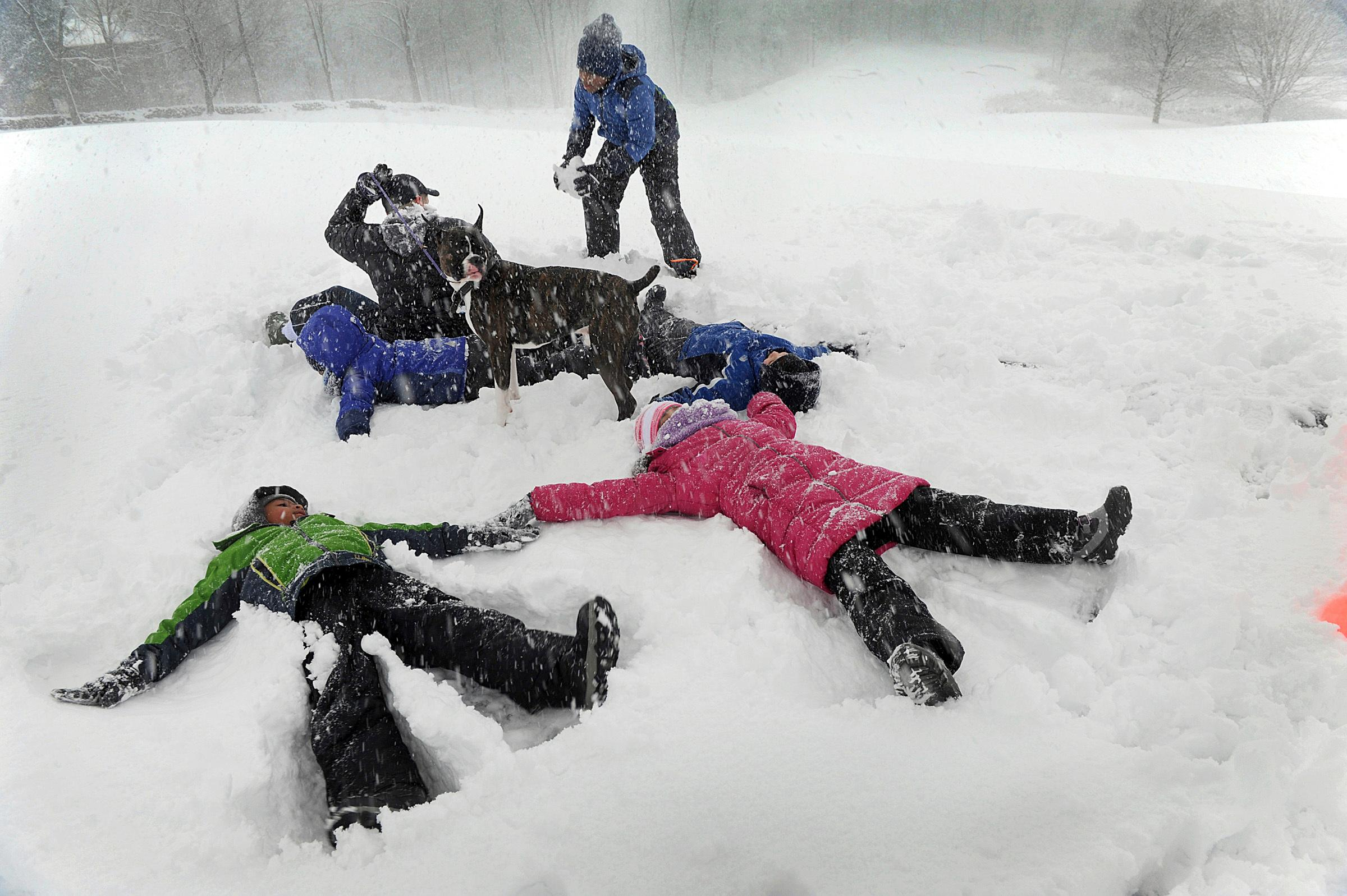 The Hilderbrand family, Gianni DeMasi-Hilderbrand, 6, front left, and Olivia Hilderbrand, 9, right, plays in the snow making snow angels at Richter Park in Danbury, Conn., during Wednesday's snowstorm, March 7, 2018. (Carol Kaliff/Hearst Connecticut Media via AP)