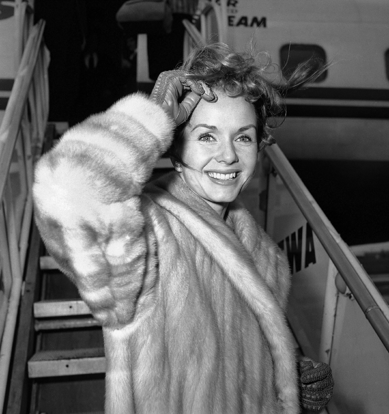 Screen actress Debbie Reynolds is a pretty wind-blown portrait as she boards airliner on March 6, 1959 in New York for Spain where she will film a new picture. She had flown in from California earlier in the day and contended with many questions about her divorced husband Eddie Fisher?s romance with Elizabeth Taylor. Said she: ?I wish them all happiness. That?s what we all want isn?t it?? (AP Photo/John Rooney)