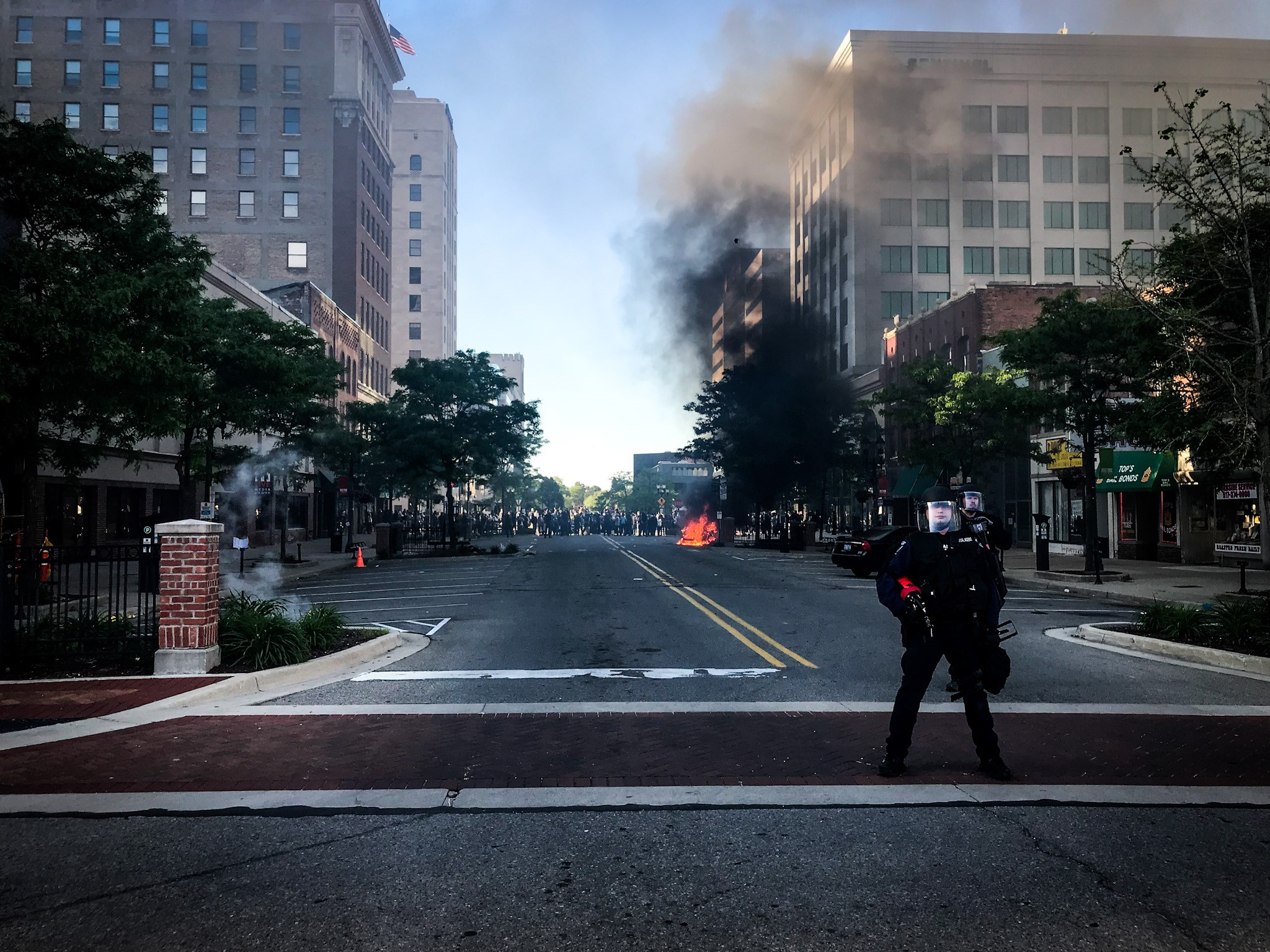 A car was completely burned on a street in Lansing after a peaceful protest turned violent and police used teargas to disperse the crowd on Sunday, May 31, 2020. (WWMT/Mikenzie Frost)