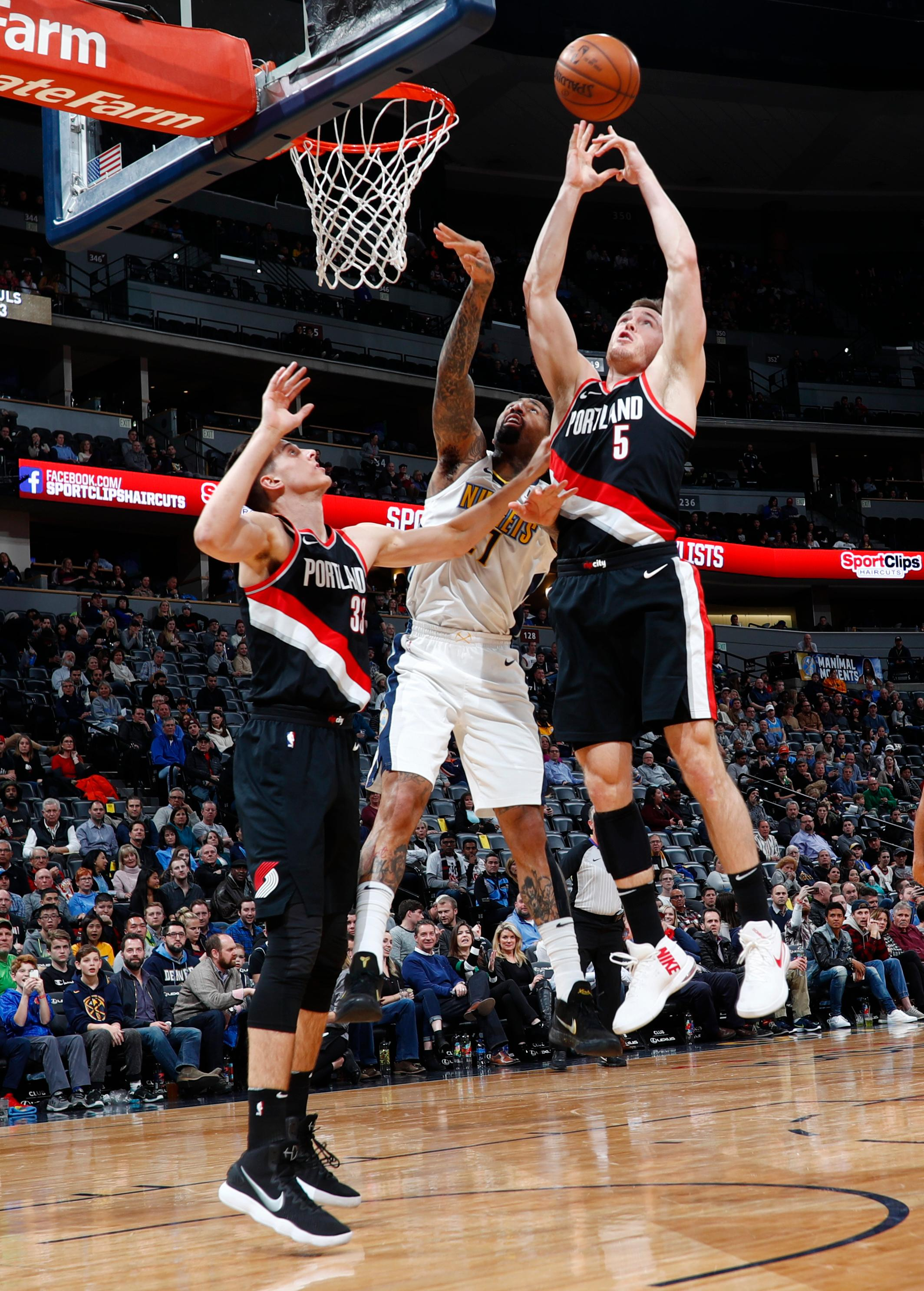 Denver Nuggets forward Wilson Chandler, center, fights for control of a rebound with Portland Trail Blazers center Zach Collins, left, and guard Pat Connaughton in the first half of an NBA basketball game Monday, Jan. 22, 2018, in Denver. (AP Photo/David Zalubowski)
