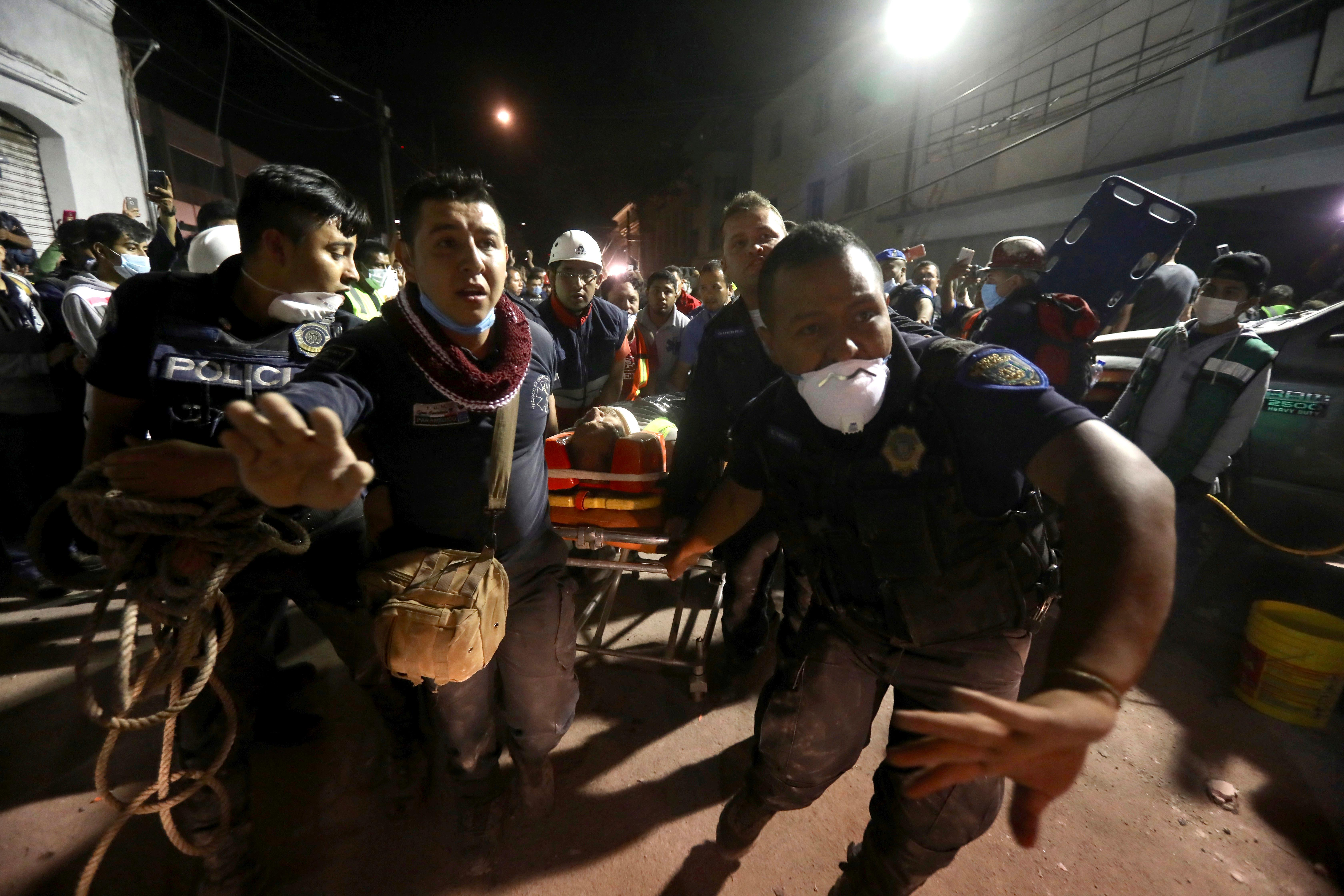 Emergency personnel rush past with a gurney carrying a victim rescued from the rubble of a building that collapsed during a 7.1 earthquake, in the Colonia Obrera neighborhood of Mexico City, Tuesday, Sept. 19, 2017. People across central Mexico already had rallied to help their neighbors as dozens of buildings tumbled into mounds of broken concrete. (AP Photo/Miguel Tovar)
