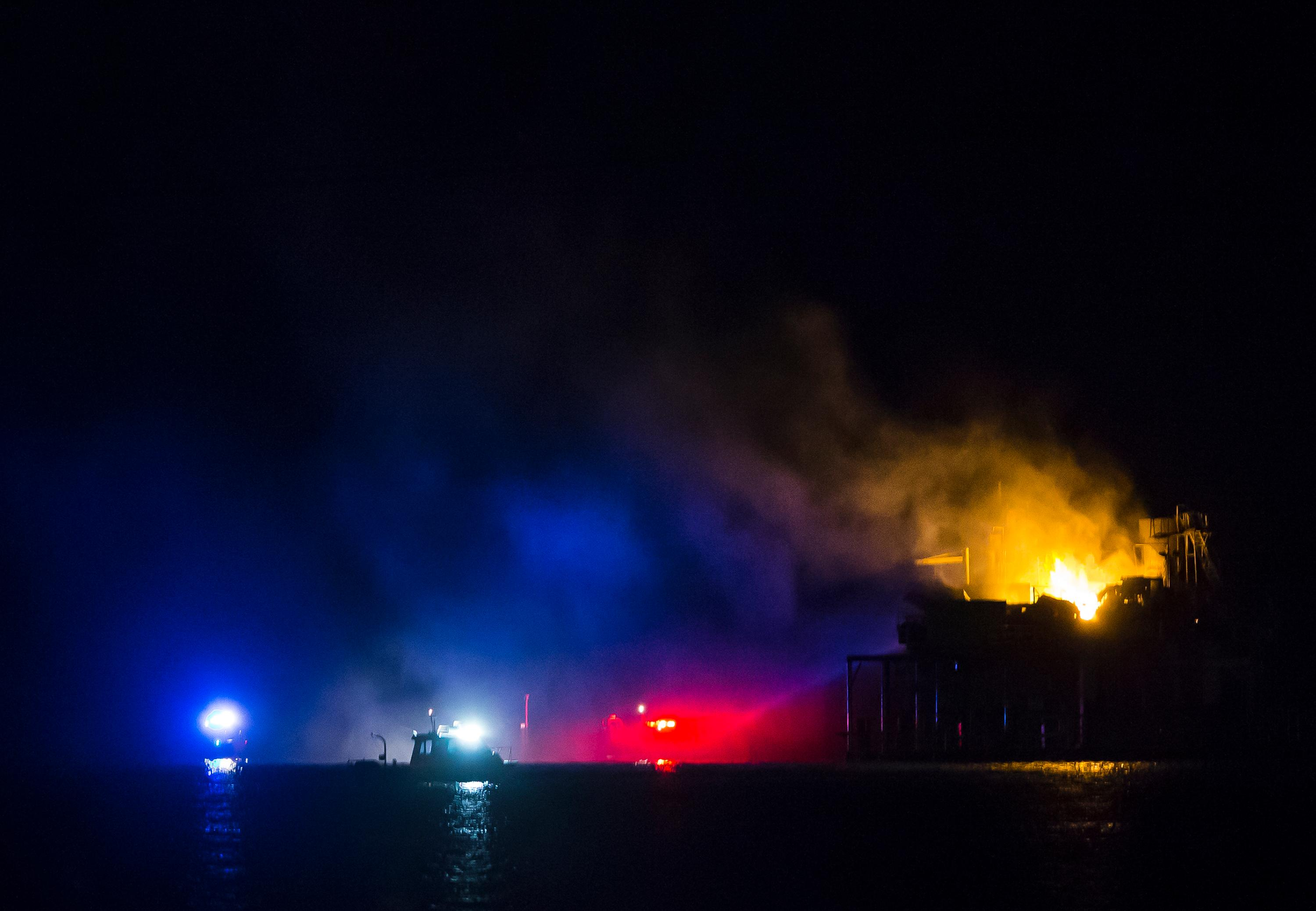 Rescue boats surround a rig in Lake Pontchartrain near New Orleans, La., after the rig exploded late on Sunday, Oct. 15, 2017. The explosion took place Sunday night in Lake Pontchartrain in St. Charles Parish, a Louisiana police department said. (Chris Granger/NOLA.com The Times-Picayune via AP)