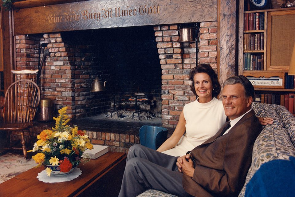 "While Billy and Ruth Graham both traveled the world, spending time at home was always important. The mantel behind them bears a German inscription that reads, ""A Mighty Fortress Is Our God."" Their home was dedicated to God, and this phrase was a powerful reminder. (Photo:{ } Billy Graham Evangelistic Association)"