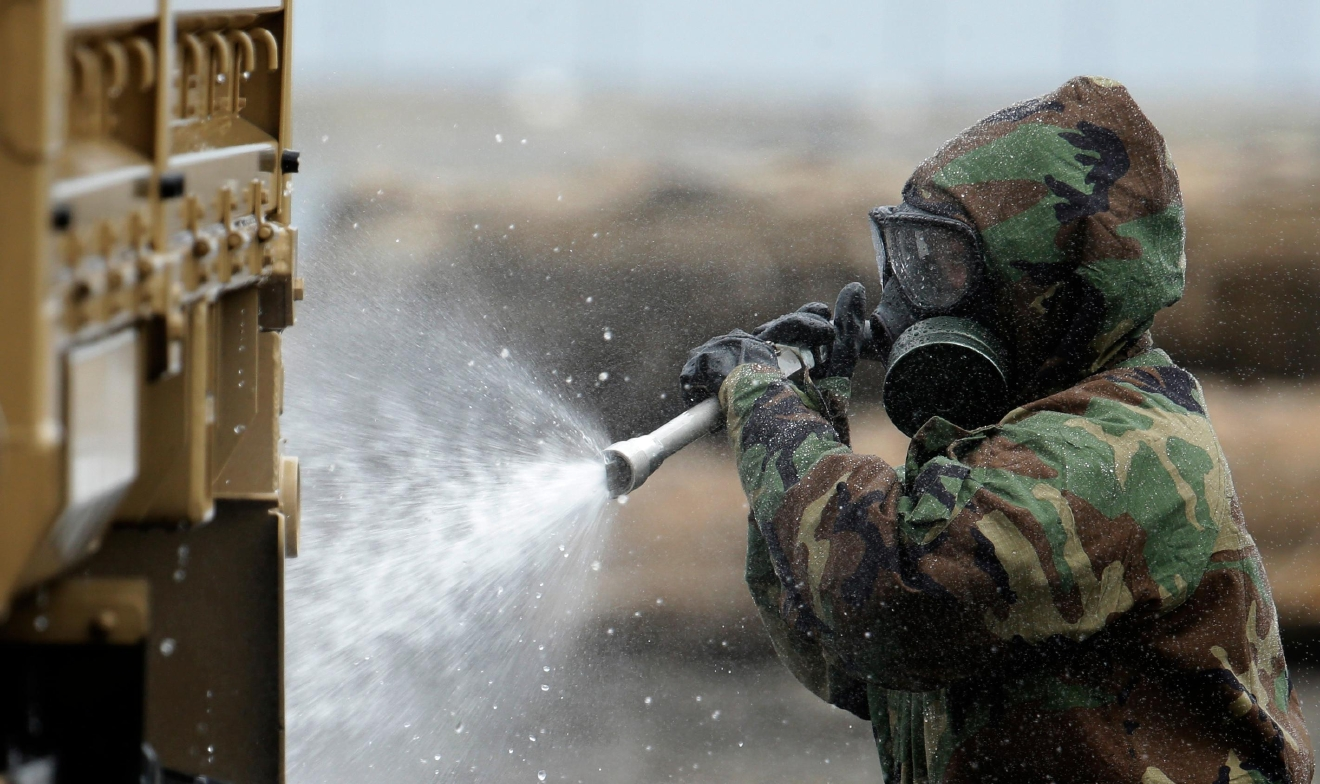 A member of the Washington Army National Guard 792nd Chemical Company from Grandview, Wash., demonstrates how a military vehicle would be decontaminated if it came in contact with polluted or hazardous substances stirred up by a tsunami, Wednesday, June 8, 2016, in Port Angeles, Wash. The exercise was part of a massive earthquake and tsunami drill called Cascadia Rising, that is built around the premise of a 9.0 magnitude earthquake 95 miles off of the coast of Oregon that results in a tsunami. (AP Photo/Ted S. Warren)
