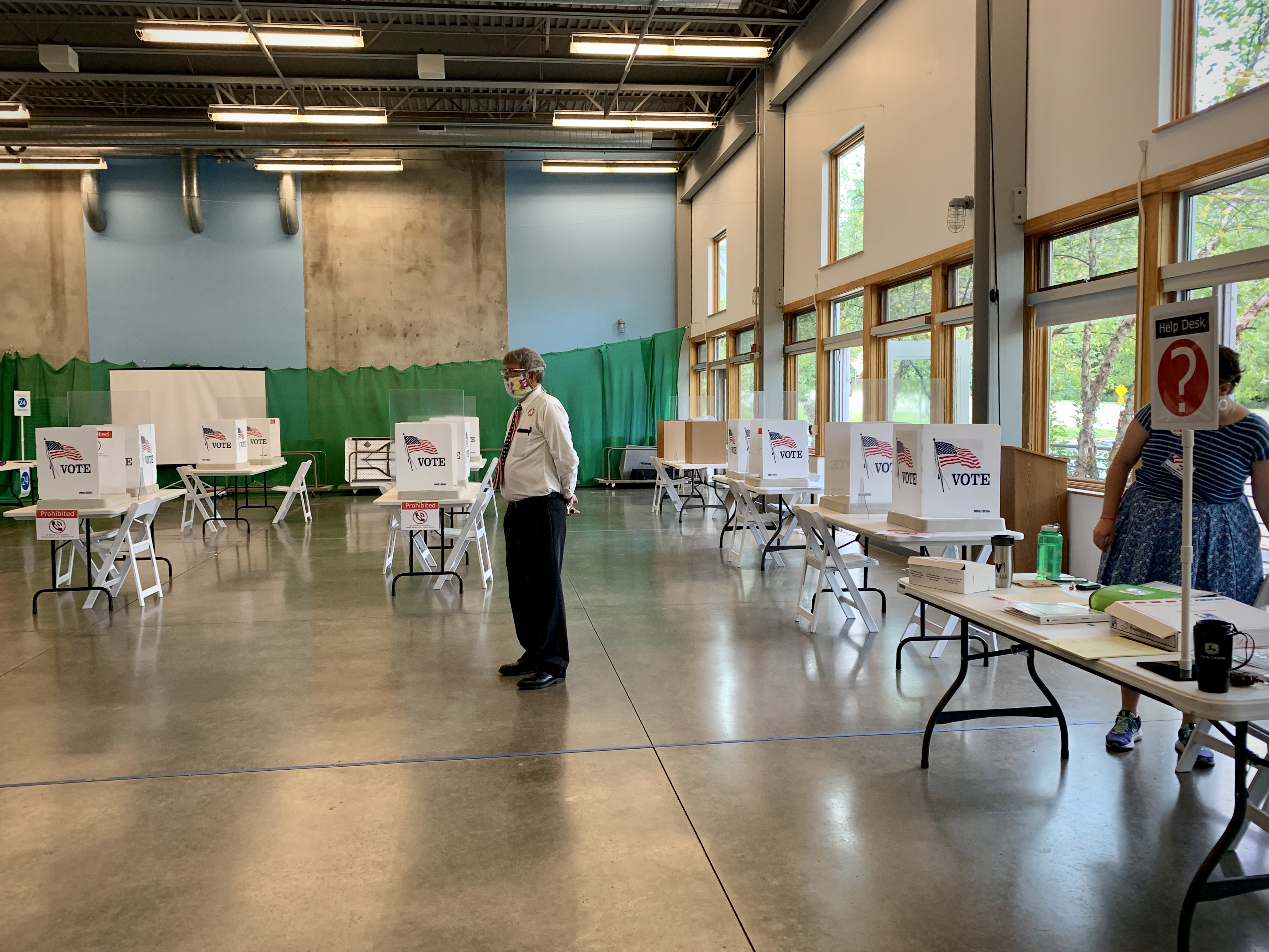 A poll worker stands amid the voting booths at the Girl Scouts of Michigan offices on West Maple Street in Kalamazoo, Michigan, on Tuesday, Aug. 4, 2020. (WWMT/Hannah Knowles)