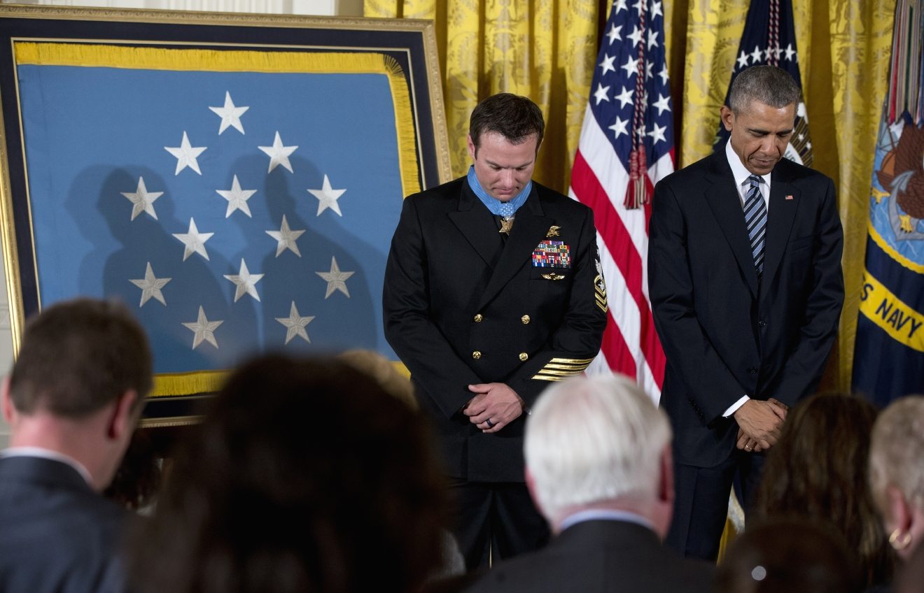 President Barack Obama and Senior Chief Special Warfare Operator Edward Byers bow their heads in prayer during a ceremony in the East Room of the White House in Washington, Monday, Feb. 29, 2016, after the president presented Byers with the Medal of honor.  U.S. Navy. Senior Chief Byers receives the Medal of Honor for his courageous actions while serving as part of a team that rescued an American civilian being held hostage in Afghanistan on December 8-9, 2012. (AP Photo/Carolyn Kaster)