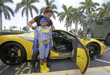 "Christina Rodriguez, rear, aka ""Shadow,"" adjusts Jaylen Hyde's, foreground, aka %u201CStriker Boy,%u201D cape as they arrive in a Ferrari at the Broward Sheriff's Office in Fort Lauderdale, Fla."