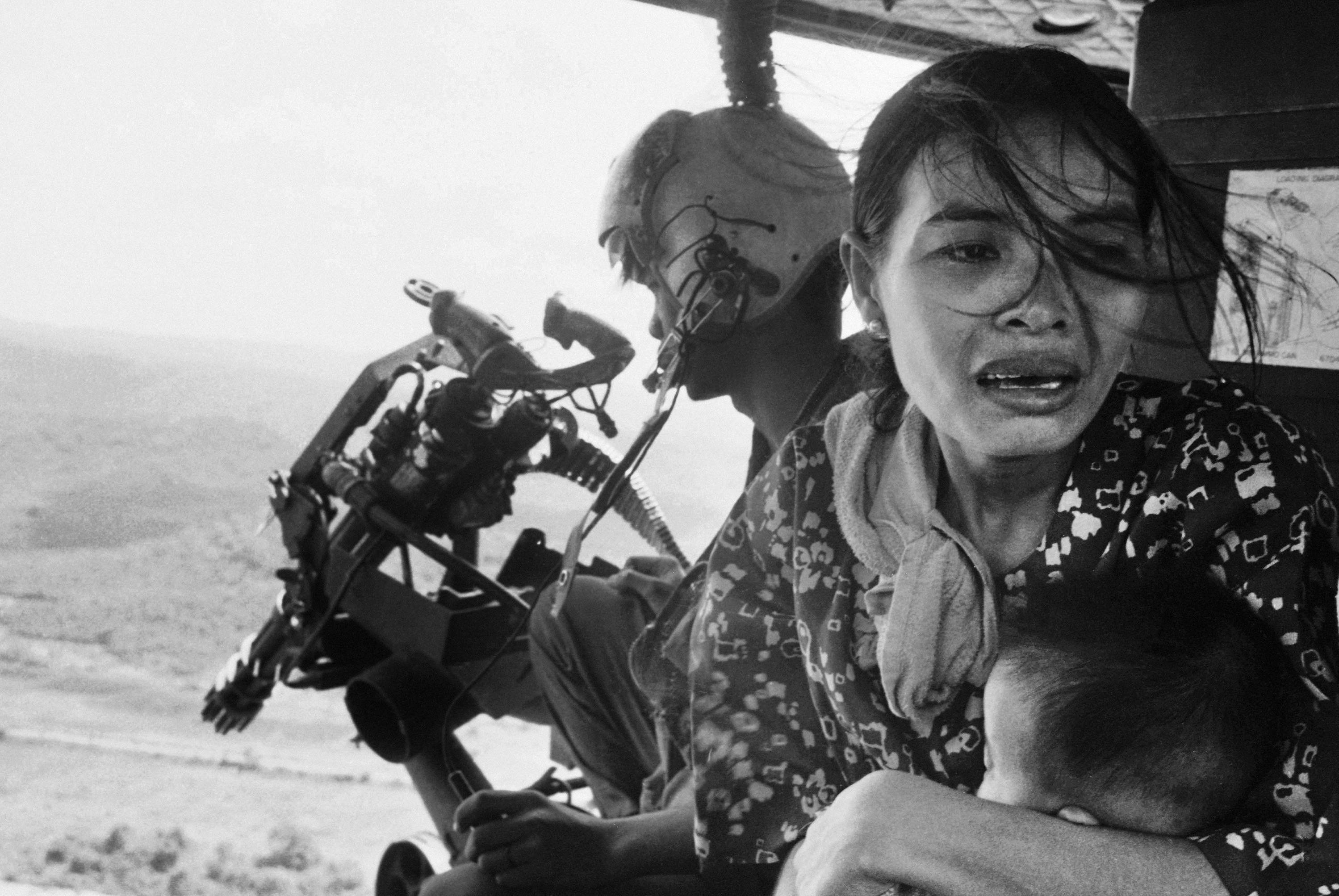 In this March 22, 1975, file photo, a refugee clutches a baby as a government helicopter gunship carries them away near Tuy Hoa, Vietnam, 235 miles northeast of Saigon. They were among thousands fleeing from Communist advances. NICK UT/THE ASSOCIATED PRESS
