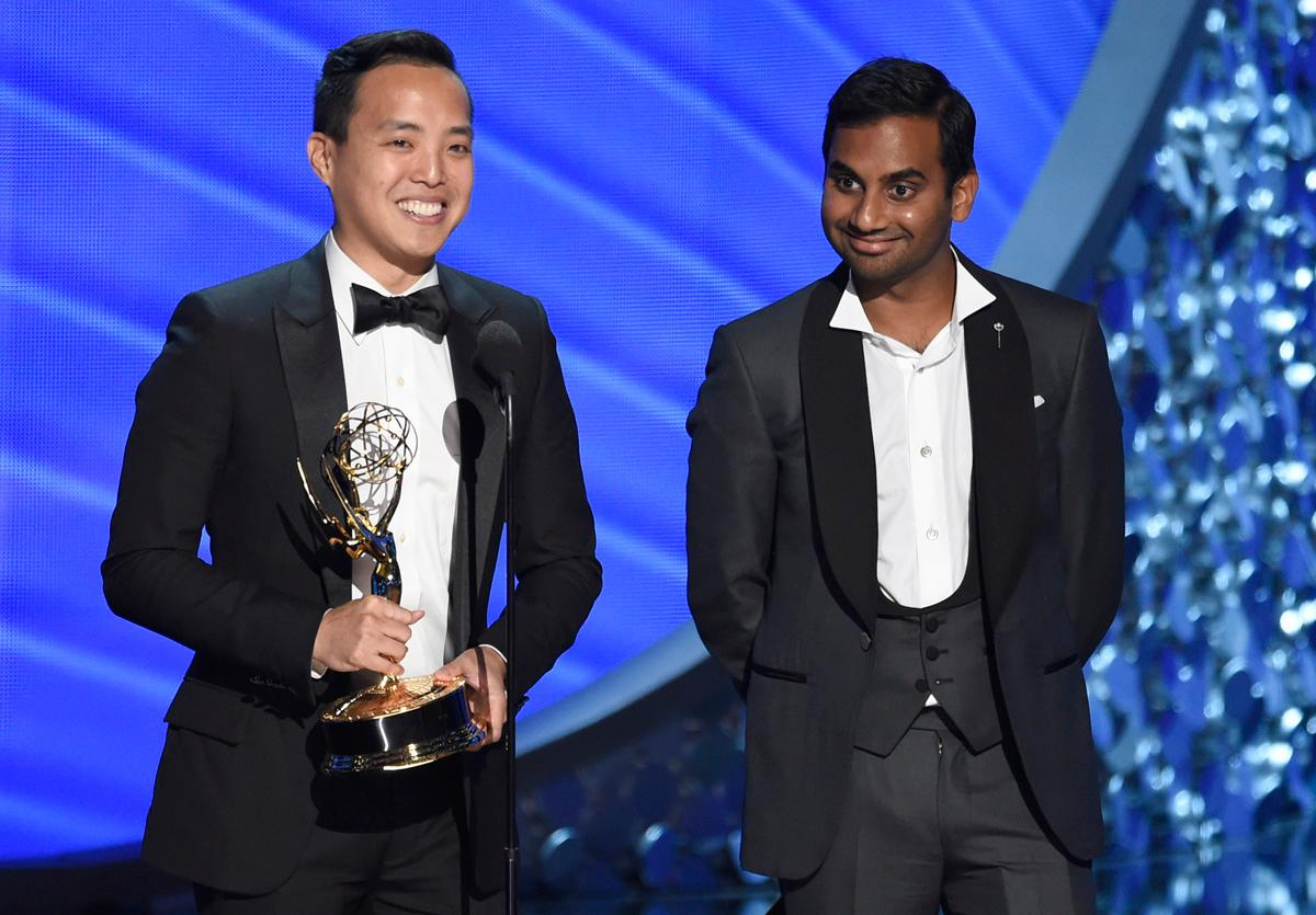 "Kelvin Yu, left, and Aziz Ansari accept the award for outstanding writing for a comedy series for ""Master of None"" at the 68th Primetime Emmy Awards on Sunday, Sept. 18, 2016, at the Microsoft Theater in Los Angeles. (Photo by Chris Pizzello/Invision/AP)"
