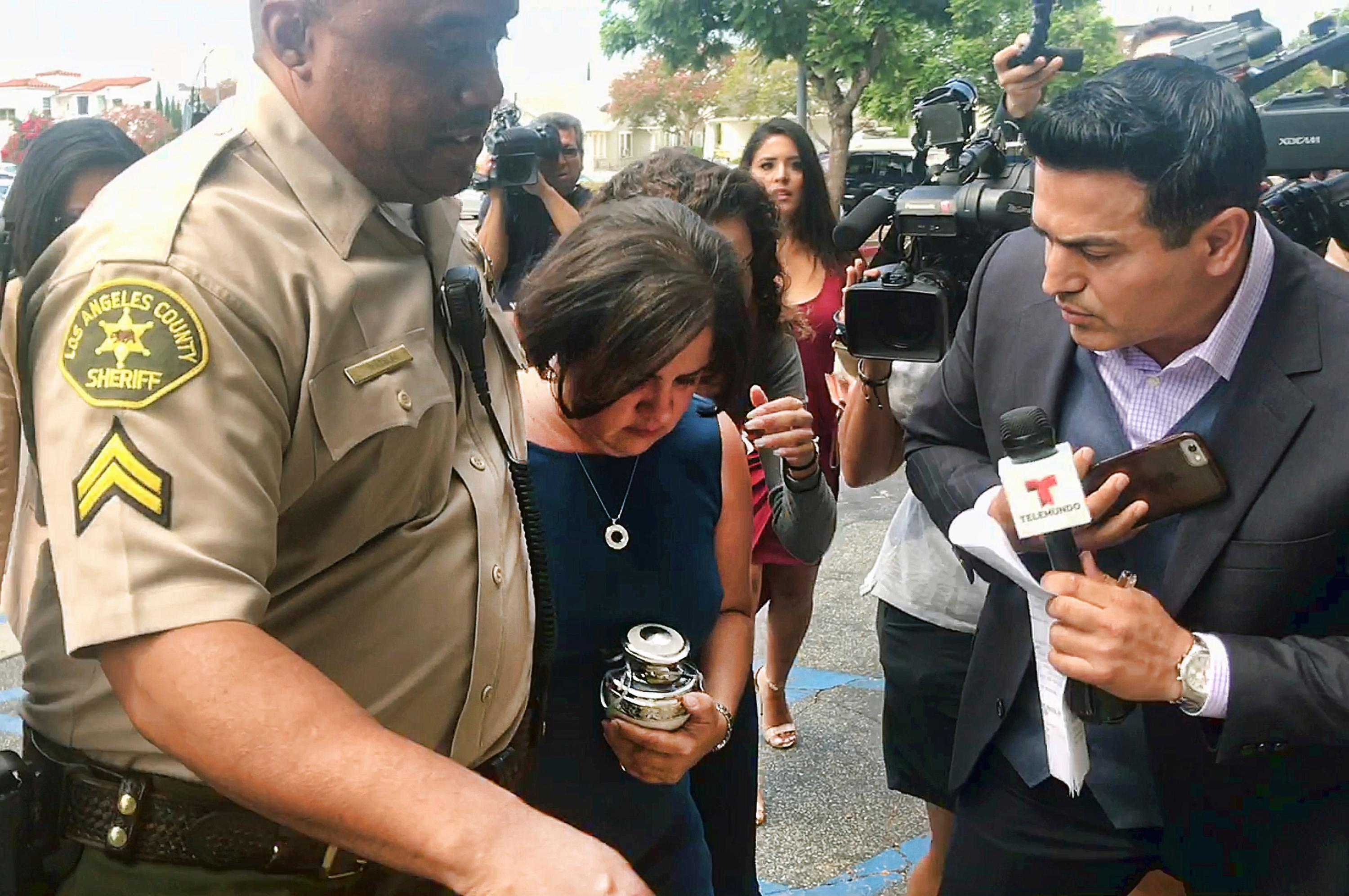 In this image taken from video, Ana Estevez, the mother of 5-year-old Aramazd Andressian Jr., carries an urn with her son's remains as she leaves a court hearing in Alhambra, Calif., Tuesday, Aug. 1, 2017. The boy's father Aramazd Andressian Sr. pleaded guilty in the killing. (AP Photo/Mike Balsamo)