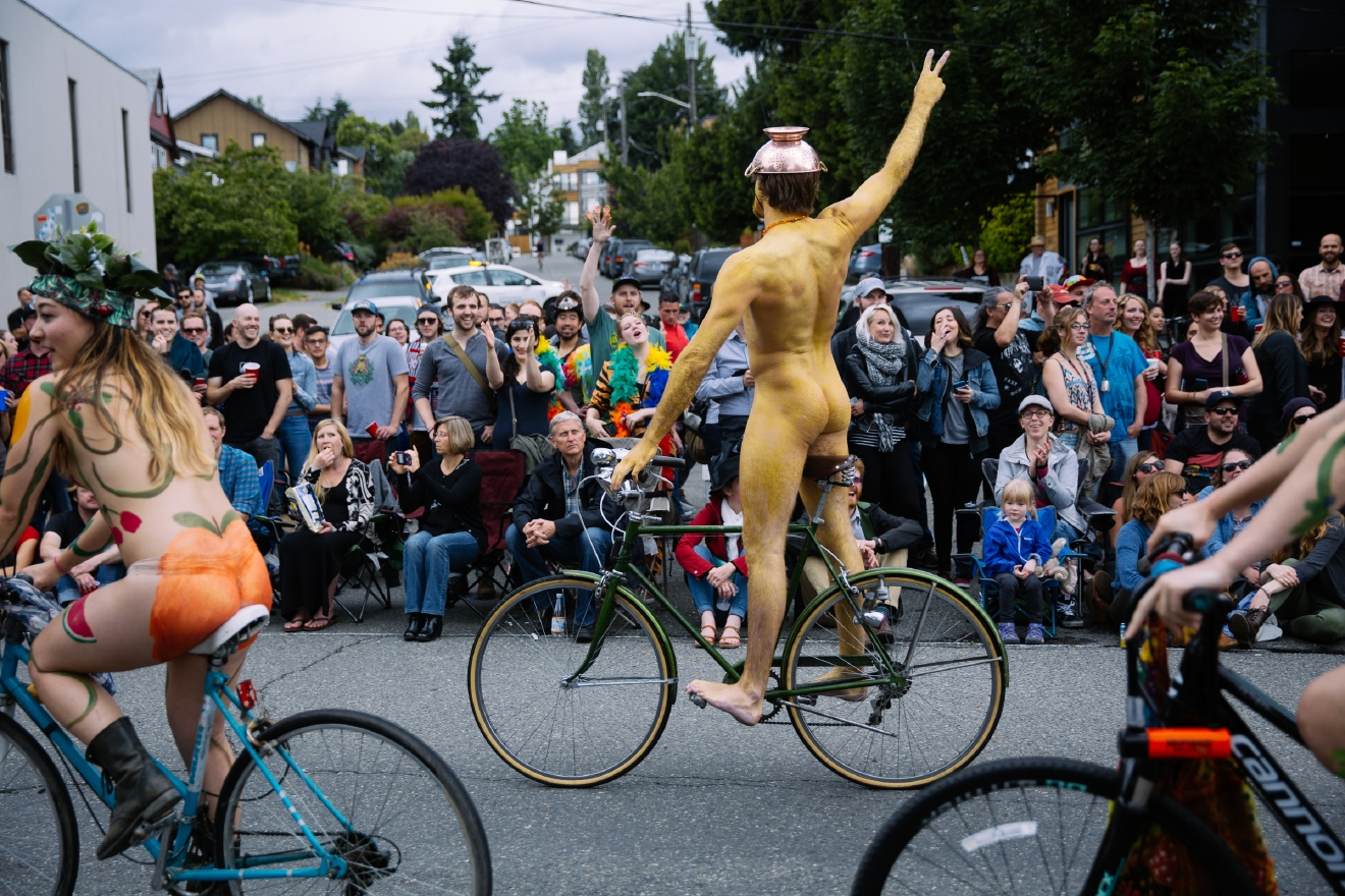 Thousands come down to the Fremont Solstice Fair for the annual Fremont Solstice Parade. Hundreds of bike riders get naked and unofficially kick off the Fremont Solstice Parade, painting their body in all types of colorful ways. Once the naked bike riders roll through musicians, dancers, clowns and lots of other quirky characters take to the parade route. June 18th (Image: Joshua Lewis / Seattle Refined)
