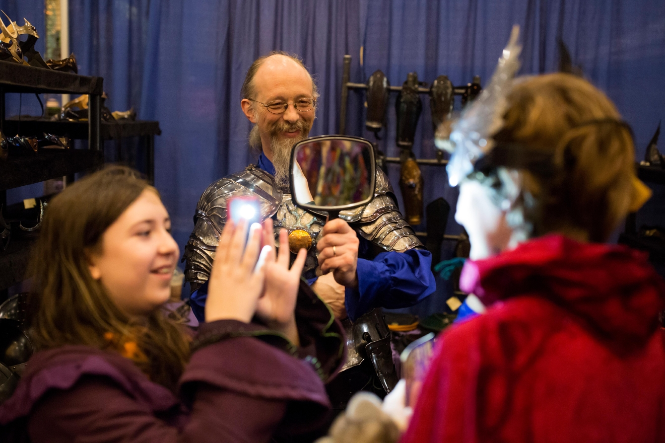 Aaron Parker of Sinister Metal Works helps a customer put on a crown at Mythicworlds Convention and Masquerades. (Sy Bean / Seattle Refined)