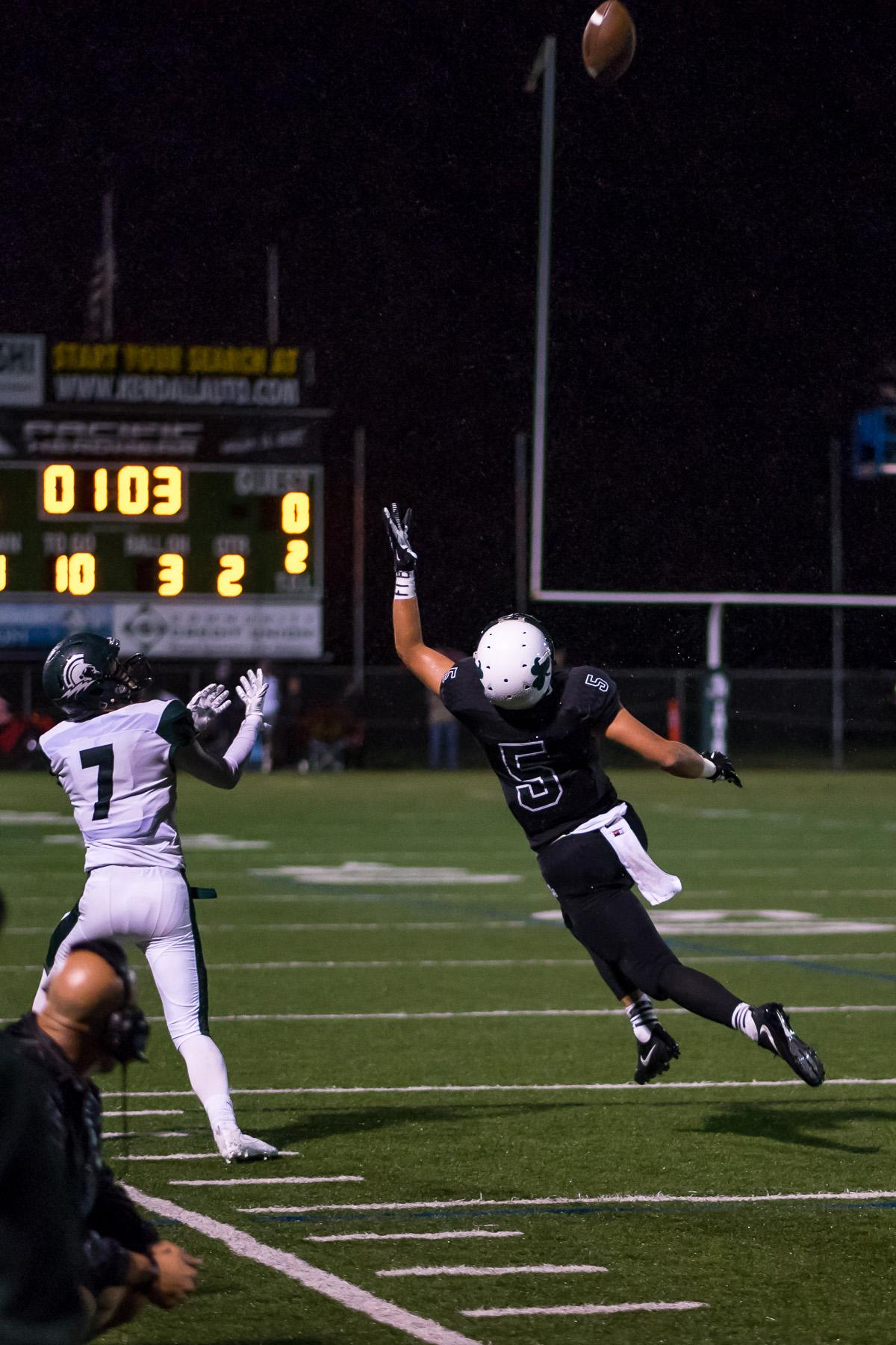 Sheldon's Patrick Herbert (#5) and West Salem's Austin Ailstock (#7) compete for a reception. On a rainy Monday evening, Sheldon defeated West Salem at home 41 – 7. The game had been postponed until Monday, September 18, due to unhealthy levels of smoke in the air caused by nearby forest fires. Photo by Kit MacAvoy, Oregon News Lab