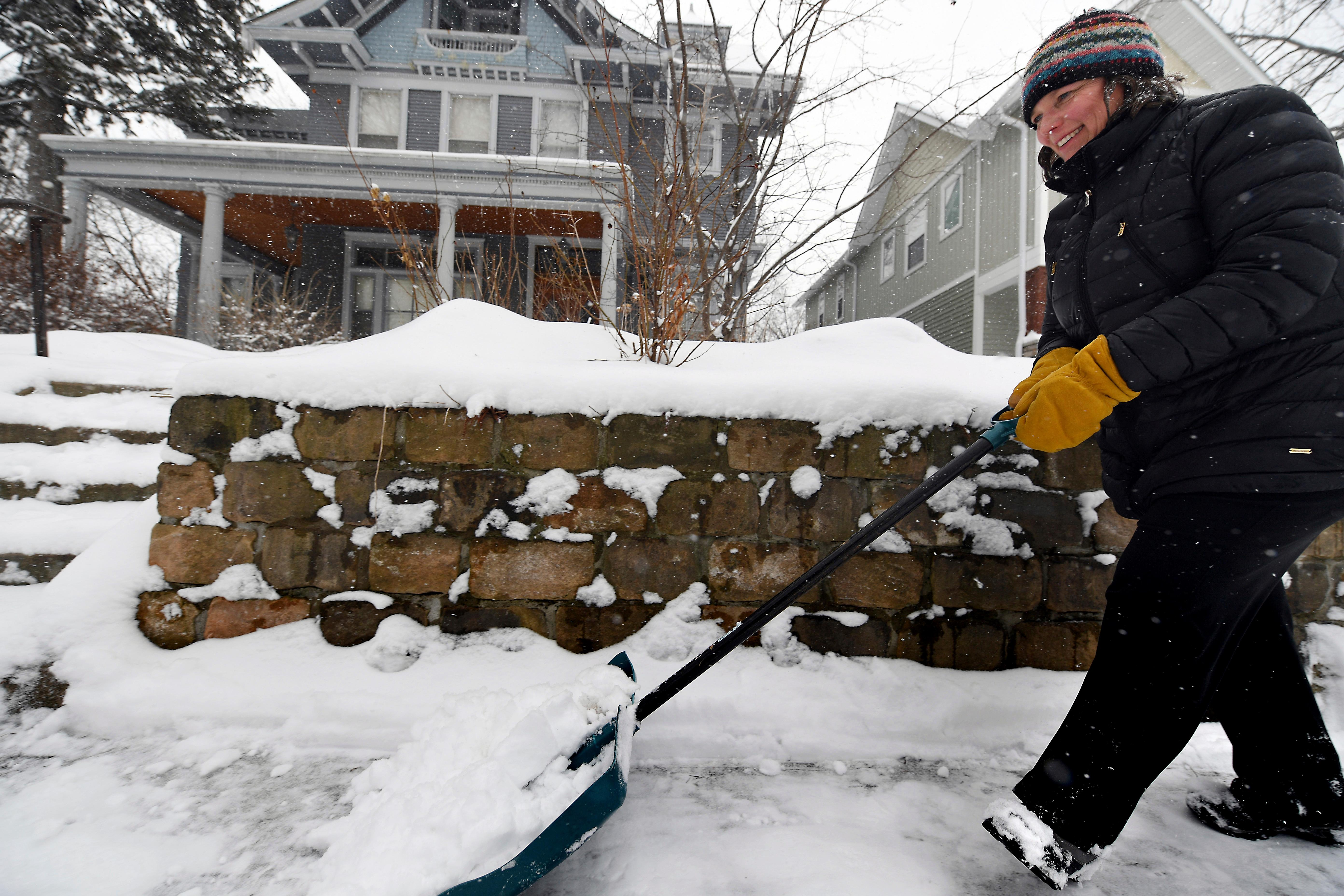 Linda Maher shovels the sidewalk in the Summit-Grand neighborhood of St. Paul, Minn. as a spring snowstorm continued across central Minnesota on Tuesday, April 3, 2018. Maher is a Lakeville school teacher and had the day off because of the storm. (John Autey /Pioneer Press via AP)