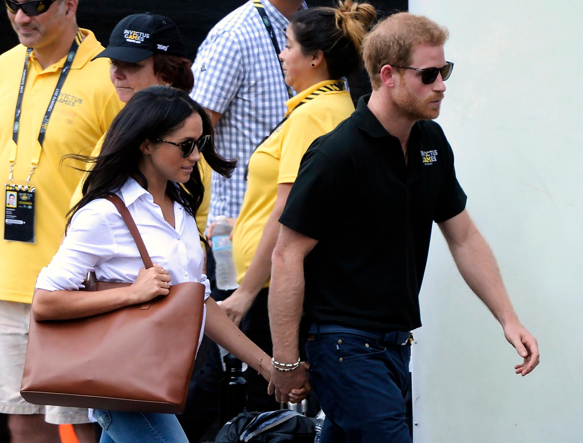 FILE - In this Monday, Sept. 25, 2017 file photo, Prince Harry and his girlfriend Meghan Markle arrive for the wheelchair tennis competition during the Invictus Games in Toronto. Palace officials announced Monday Nov. 27, 2017, Prince Harry and Meghan Markle are engaged, and will marry in the spring. (Nathan Denette/The Canadian Press via AP, File)
