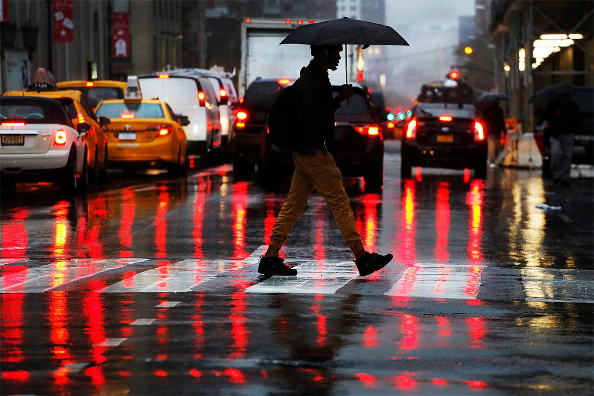 An early morning commuter carries an umbrella during a rainfall, Tuesday, Nov. 15, 2016, in New York. (AP Photo/Mark Lennihan)