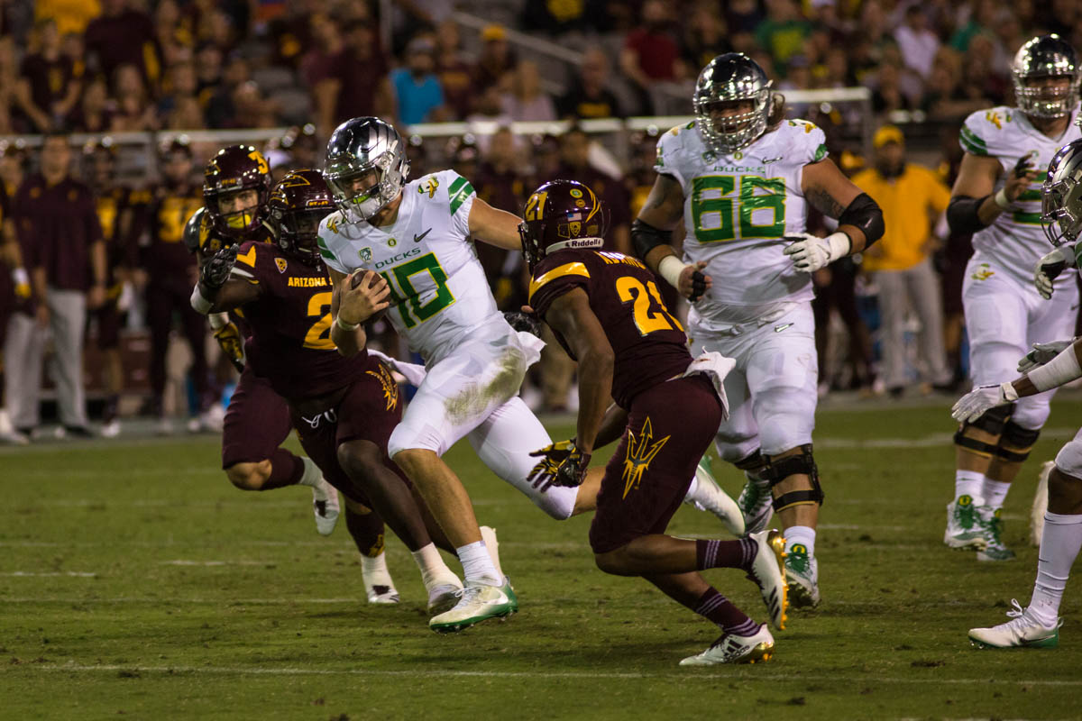 Oregon quarterback Justin Herbert (#10) runs between Arizona State tacklers. The Oregon Ducks fell to 0-1 in conference play with their first loss on the road to the Arizona State Sun Devils in Tempe, Ariz.  Photo by Austin Hicks, Oregon News Lab